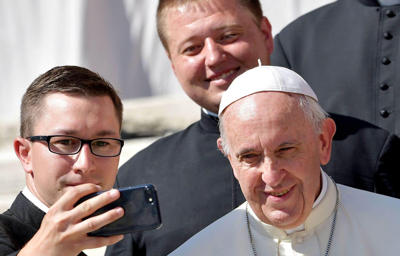 Malgré la tourmente dans laquelle l'Église est plongée depuis des mois, le pape François a pris un moment mercredi pour poser avec un jeune prêtre sur la place Saint-Pierre du Vatican.