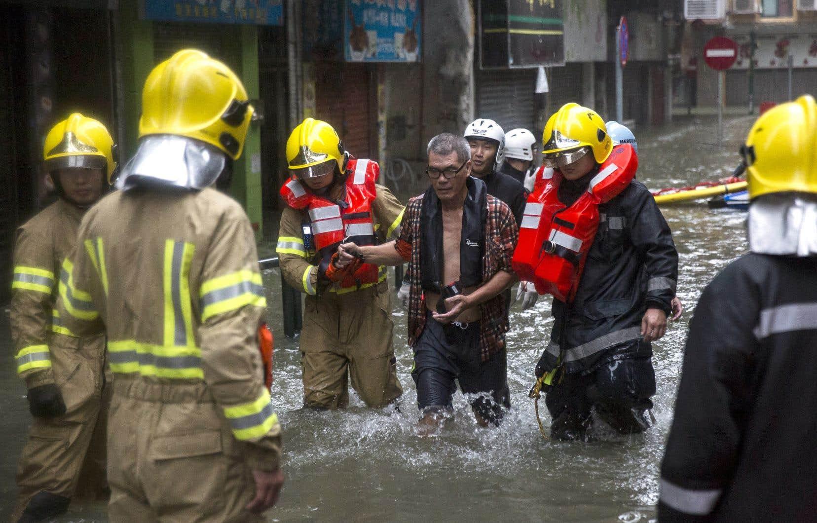 Un commerçant a été sauvé par des pompiers dans une zone fortement inondée de Macao dimanche.