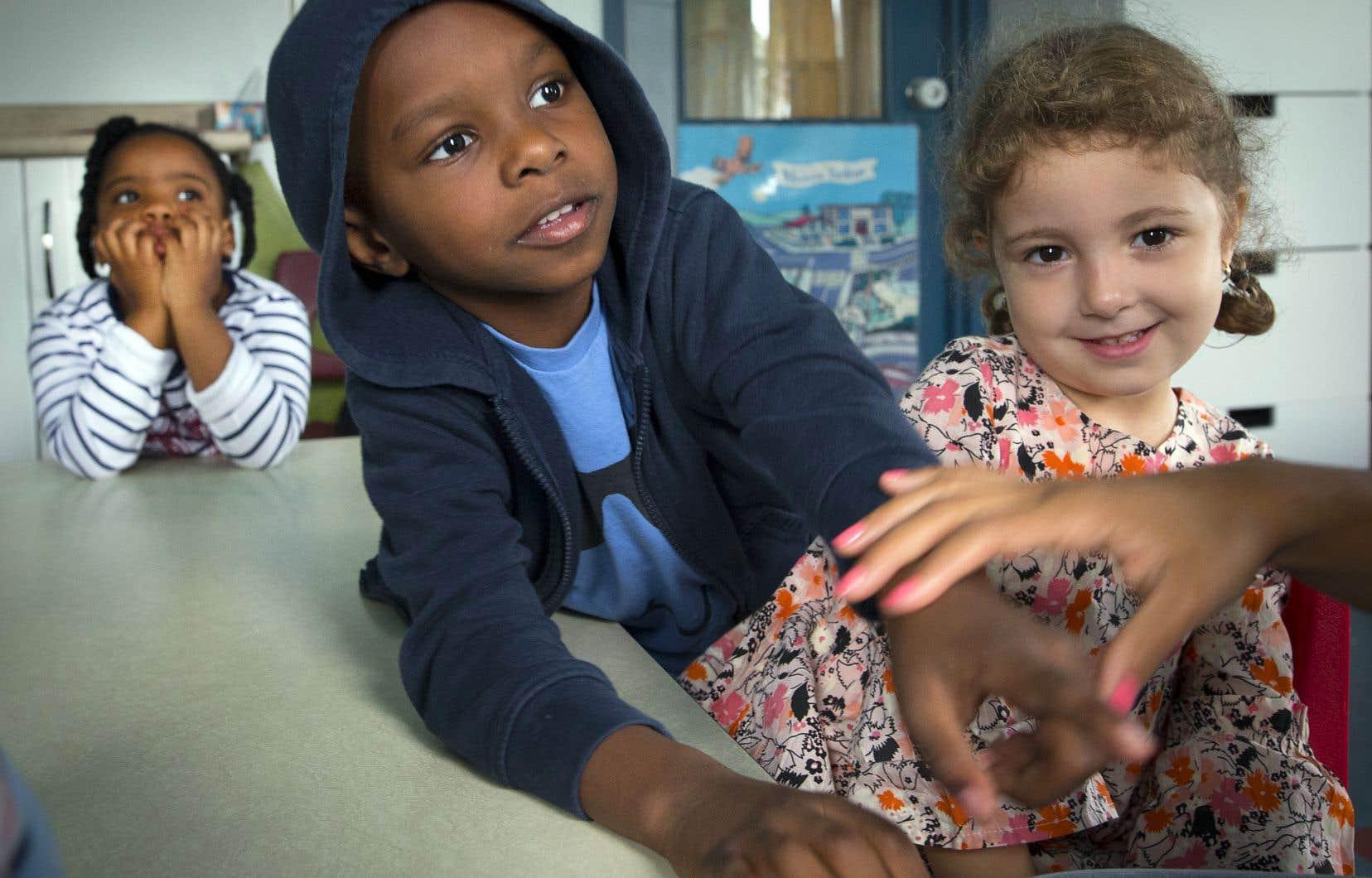 Au CPE L'Oasis des enfants, dans Montréal-Nord, Yara, Noah et Kae'lysha attendent les consignes de l'éducatrice pour la prochaine activité.