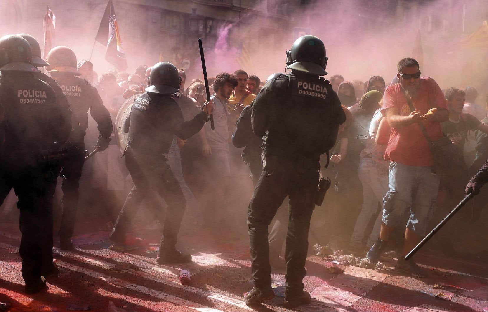 Des manifestants ont aspergé les policiers barcelonais de poudre colorée, projetant dans les airs un épais nuage arc-en-ciel.