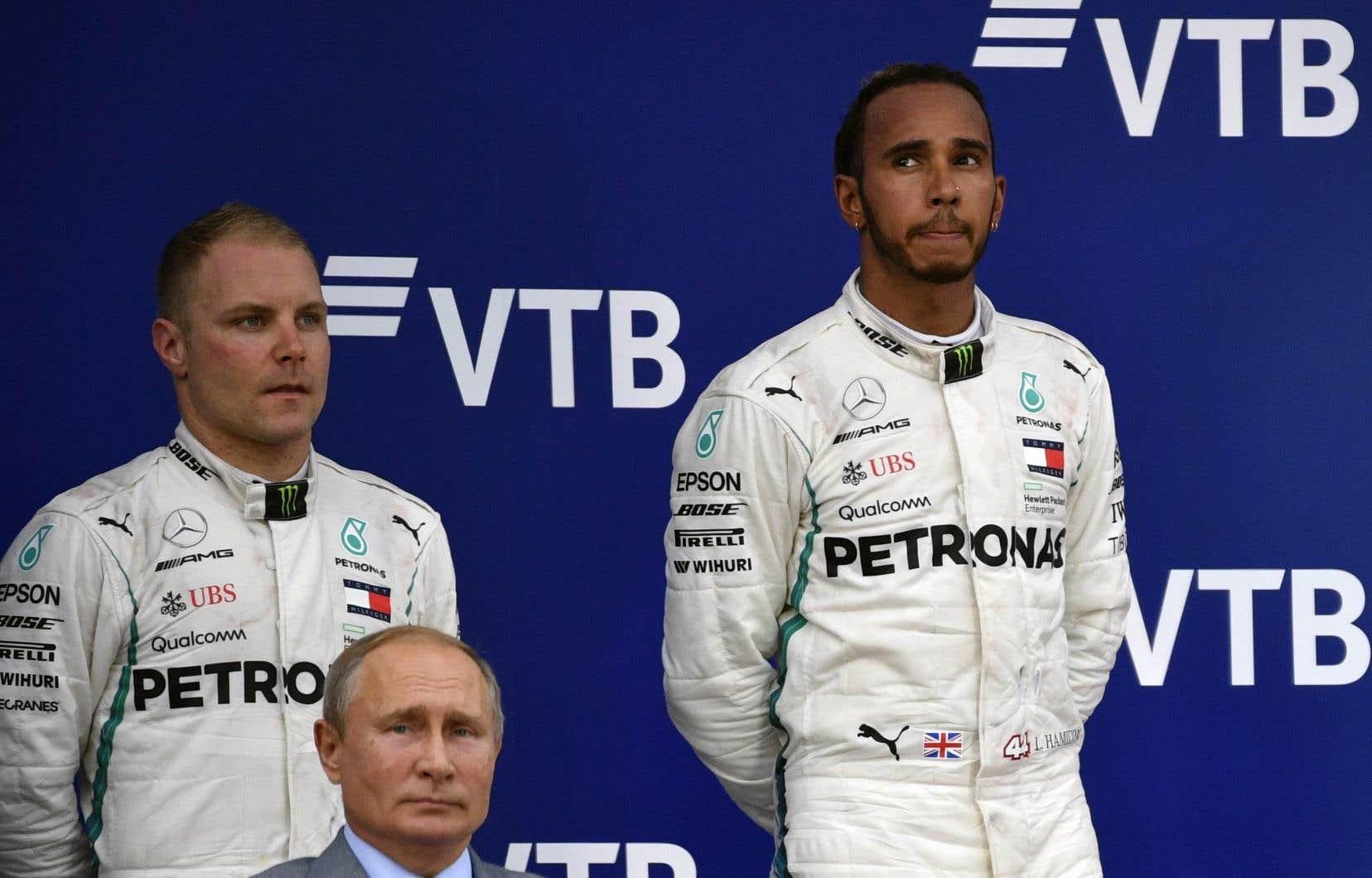 Le Britannique Lewis Hamilton (à droite) et le Finlandais Valtteri Bottas se tiennent sur le podium à côté du président russe Vladimir Poutine après le Grand Prix de Formule 1 de Russie,sur le circuit de Sotchi.