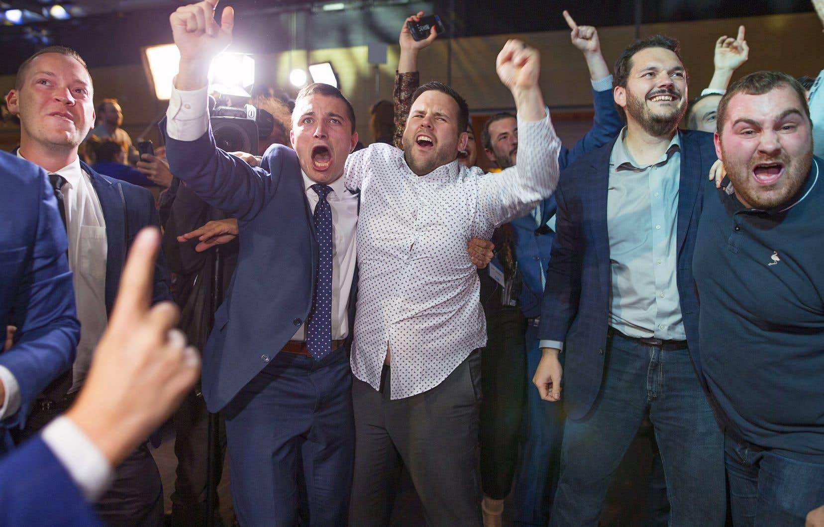 Un groupe de partisans de la Coalition avenir Québec au rassemblement de Québec. Une demi-heure après la fermeture des bureaux de vote, la nouvelle affaire politique était réglée: la CAQ obtenait la majorité des sièges à l'Assemblée nationale.