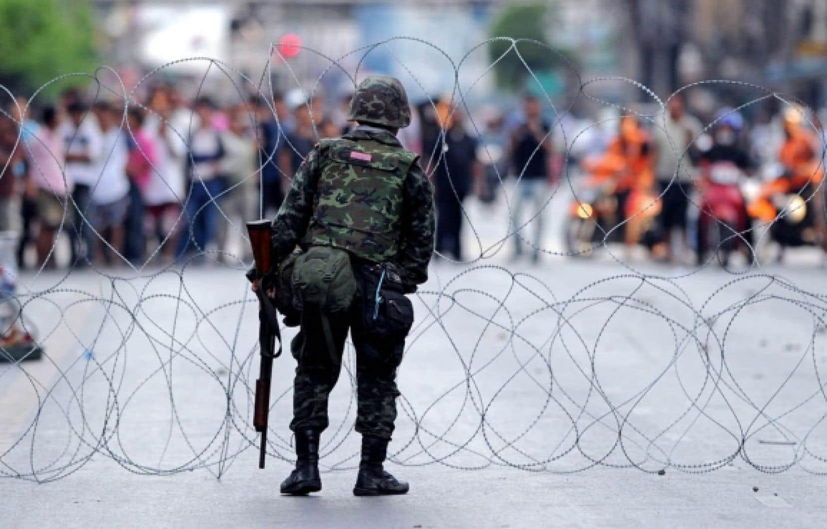 Un soldat thaïlandais dresse une clôture de fils barbelés entre l'armée et les chemises rouges. Les manifestants, pour la plupart issus de la petite bourgeoisie de province, en ont assez d'être méprisés par les «élites», ces aristocrates de Bangkok qui exhibent leur titre de noblesse ou ces bureaucrates condescendants, habitués à jouer de leur pouvoir.