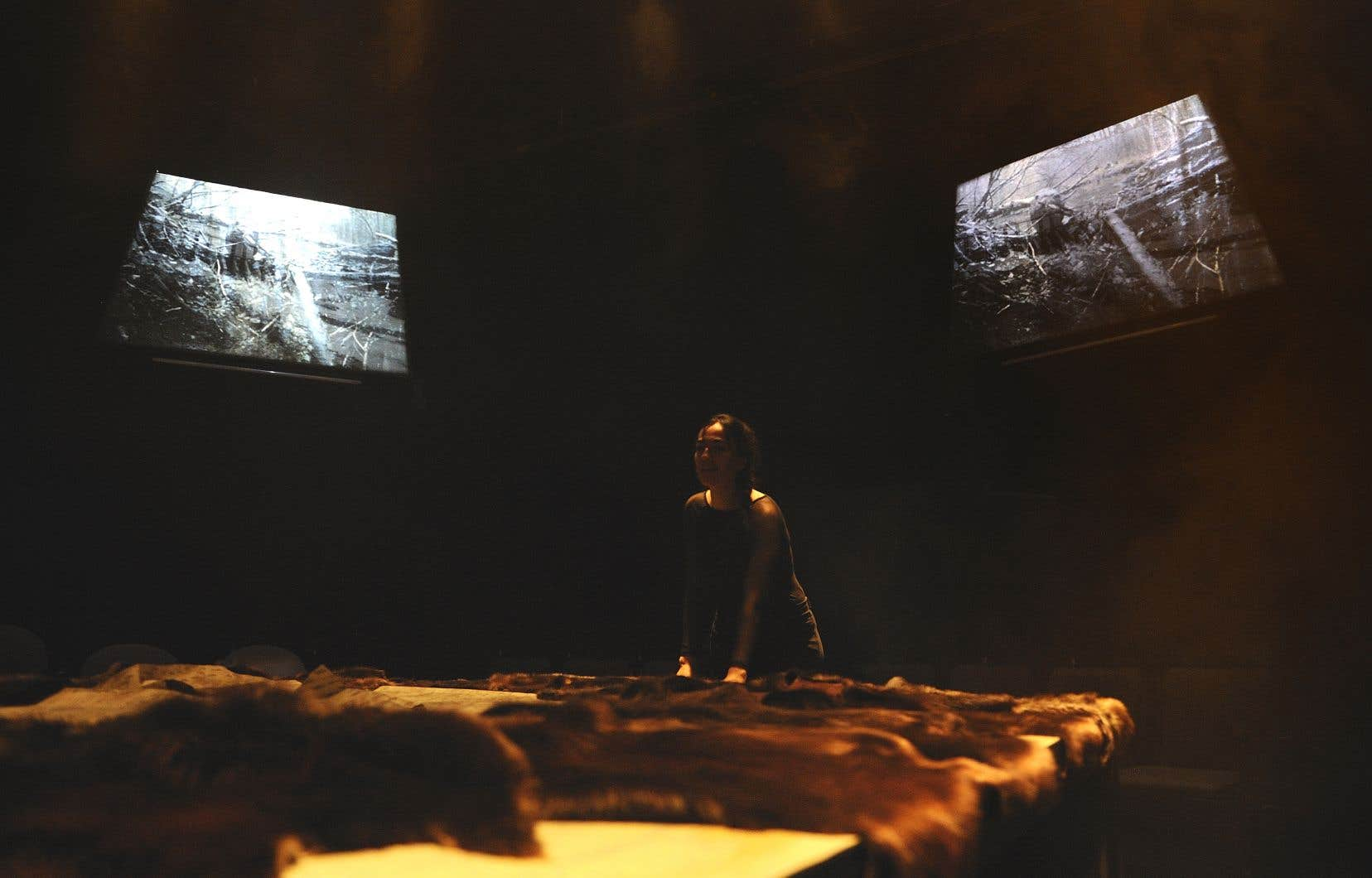 Au centre de la salle, sur une petite scène surélevée, un pentagone entouré d'écrans et de spectateurs, recouvert de peaux de castor et d'écorces de bouleau, Monnet défend son texte avec toute la conviction nécessaire.