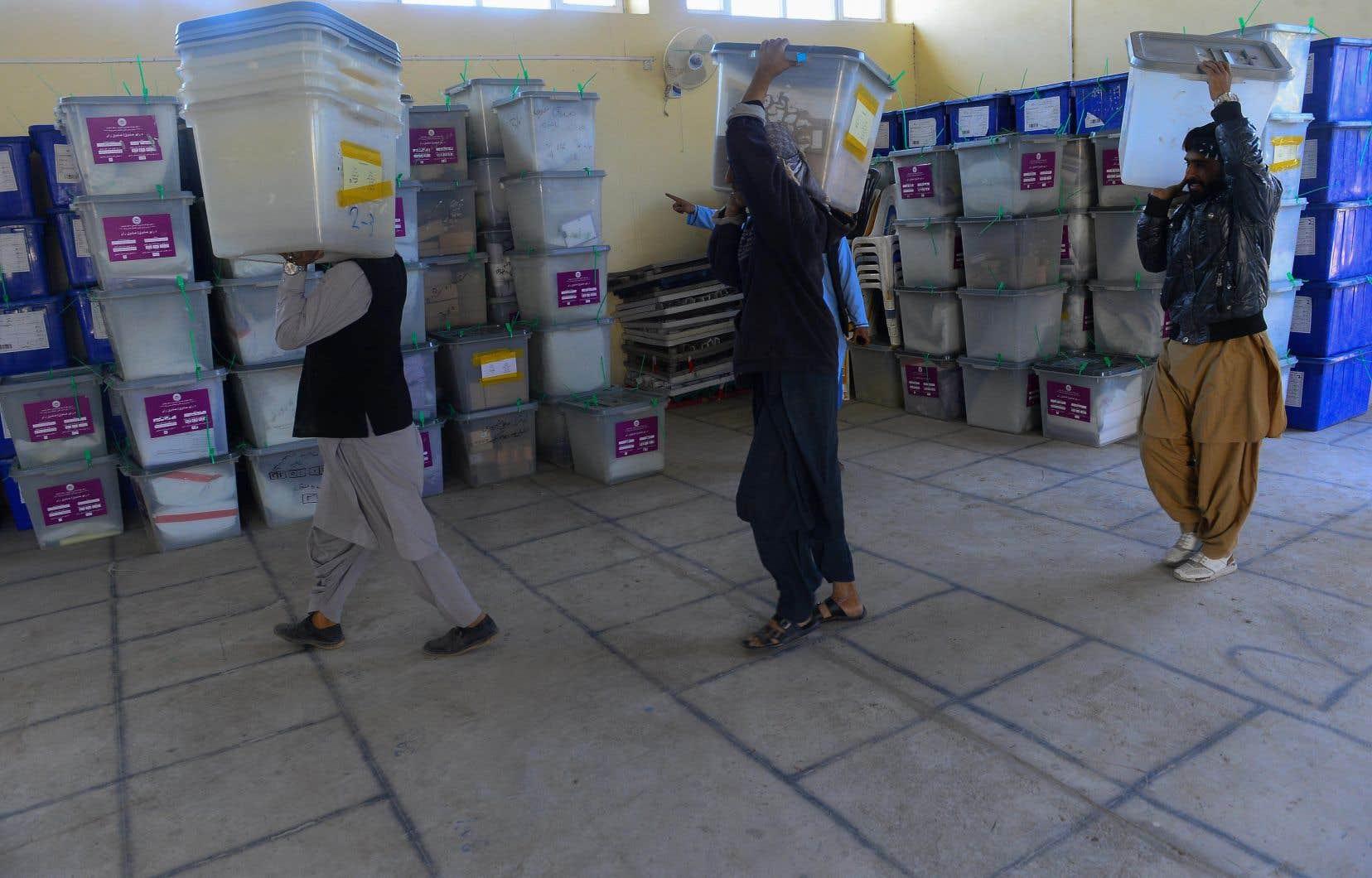 Des employés de la Commission électorale indépendante afghane transportent des urnes dans un entrepôt après le dépouillement du scrutin lors des élections législatives du pays, à Herat, le 21 octobre 2018.