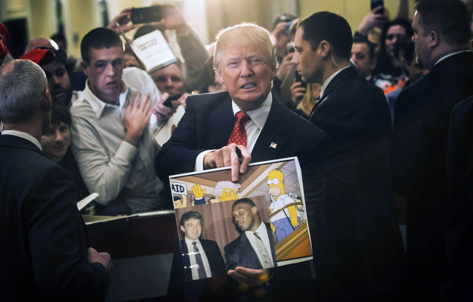 Donald Trump tient une photo le représentant avec Mike Tyson et une autre le représentant dans «Les Simpson». En effet, la série avait mis en scène la victoire du président américain dans un de ses épisodes.