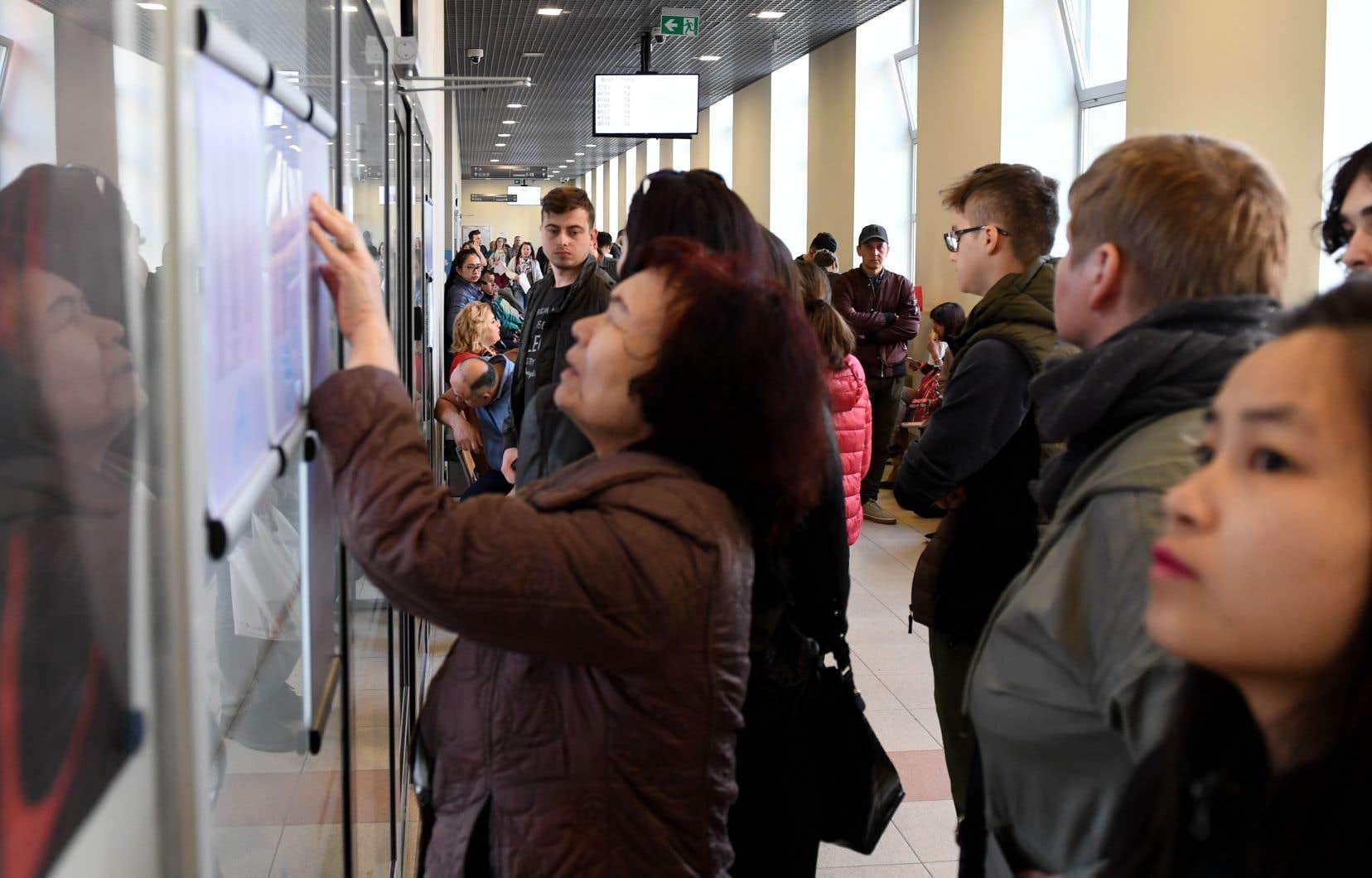 Des immigrants regardent des tableaux d'affichage au ministère polonais des Affaires étrangères, à Varsovie, où les nouveaux arrivants peuvent obtenir des permis de résidence et de travail.