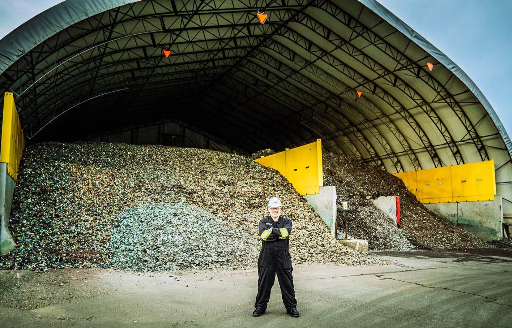 <p>Martin Carli devant une montagne de pièces d'appareils électroniques en attente d'être traiteés et recyclées</p>