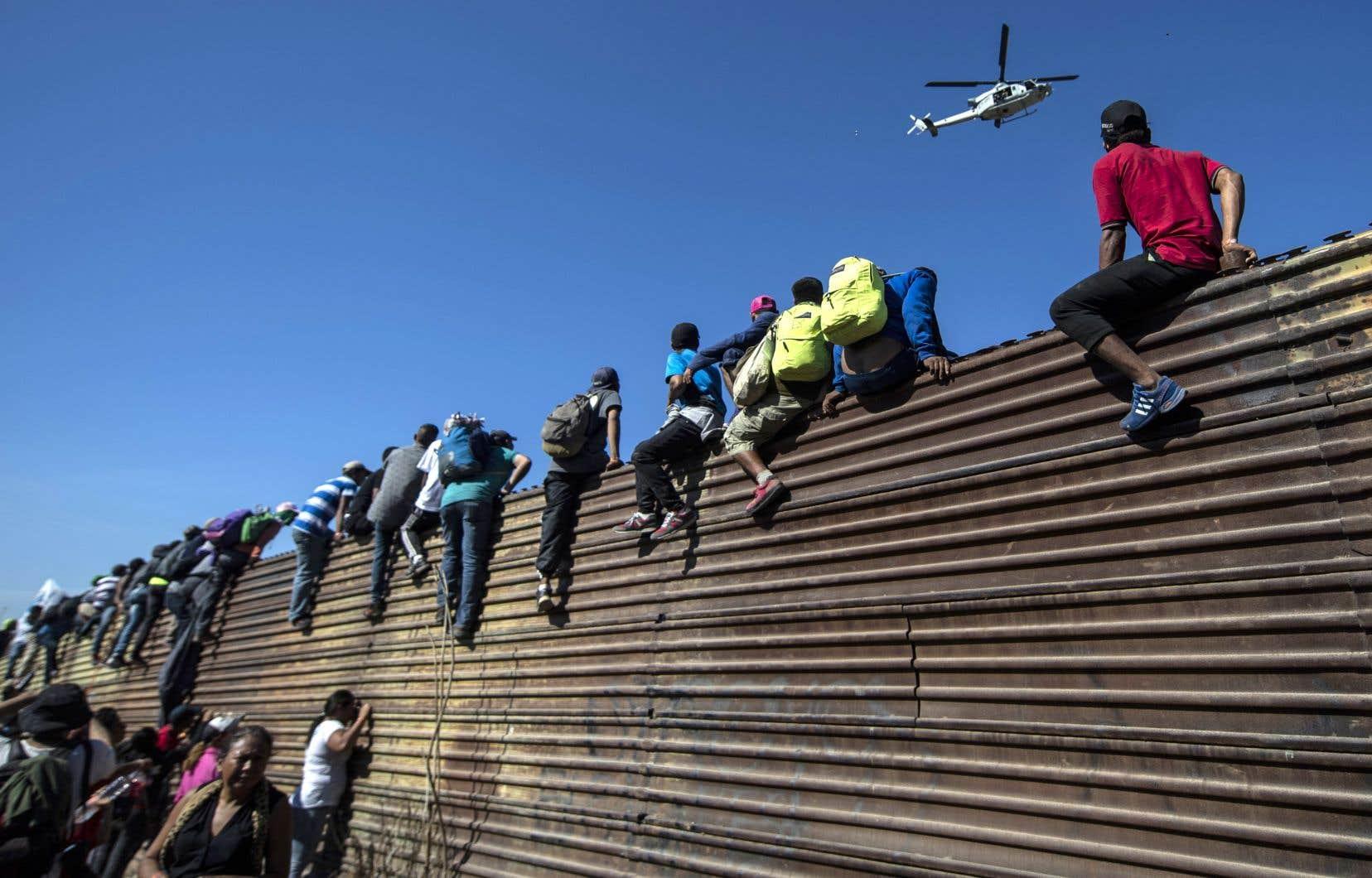 Des migrants escaladent la frontière à Tijuana.