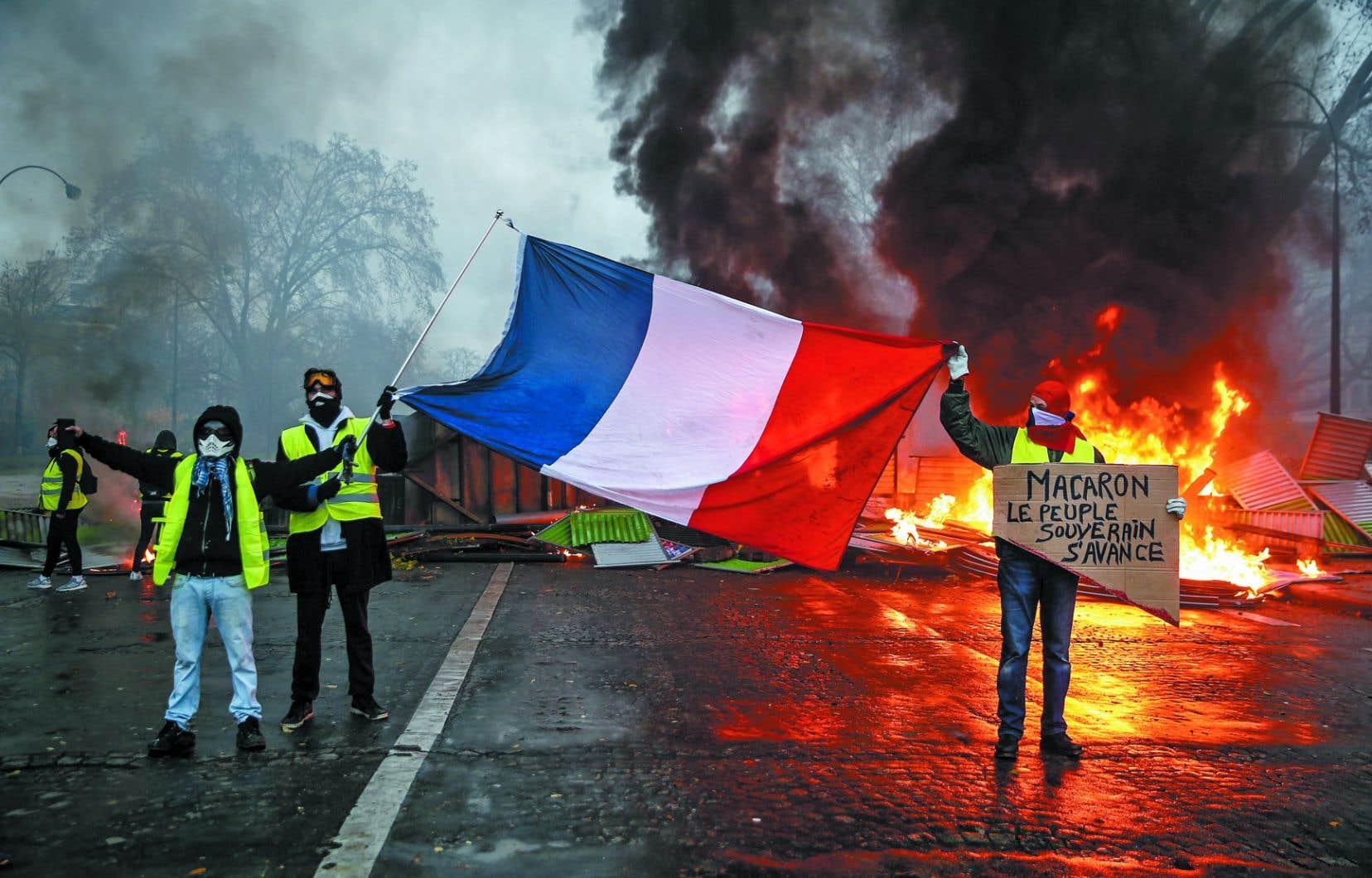 Des manifestants arborent un drapeau français près d'une barricade en feu durant le rassemblement national des gilets jaunes le 1erdécembre, près de Paris. Les annonces du gouvernement mardi n'ont pas calmé la révolte.