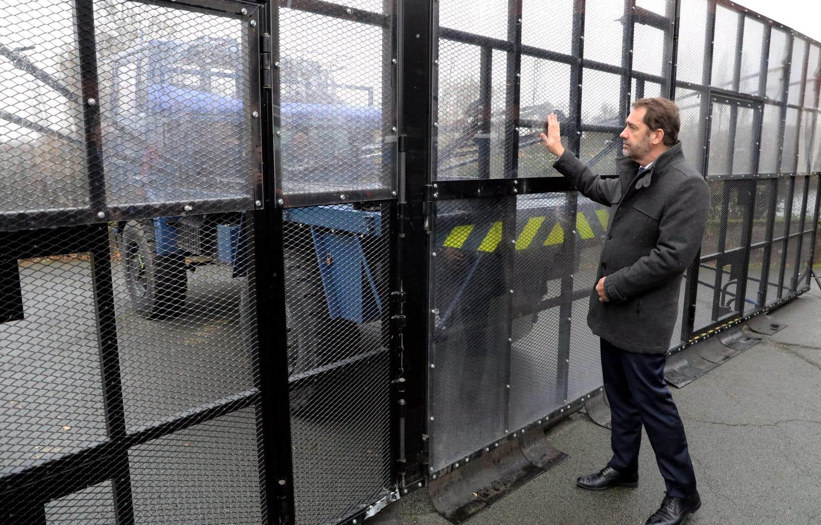 Le ministre français de l'Intérieur, Christophe Castaner, examine une barrière mobile de l'unité blindée de la Gendarmerie mobile, le 7 décembre 2018 à Versailles-Satory, à l'ouest de Paris.