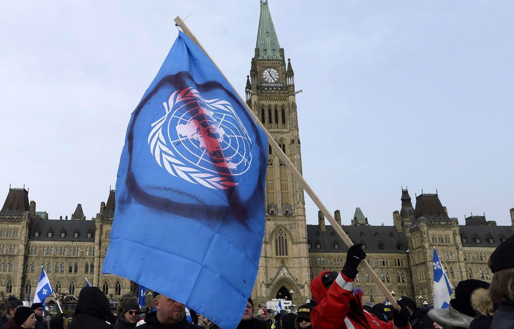 Des centaines de militants opposés à l'adhésion du Canada au Pacte de l'Onu se sont réunis devant le Parlement.