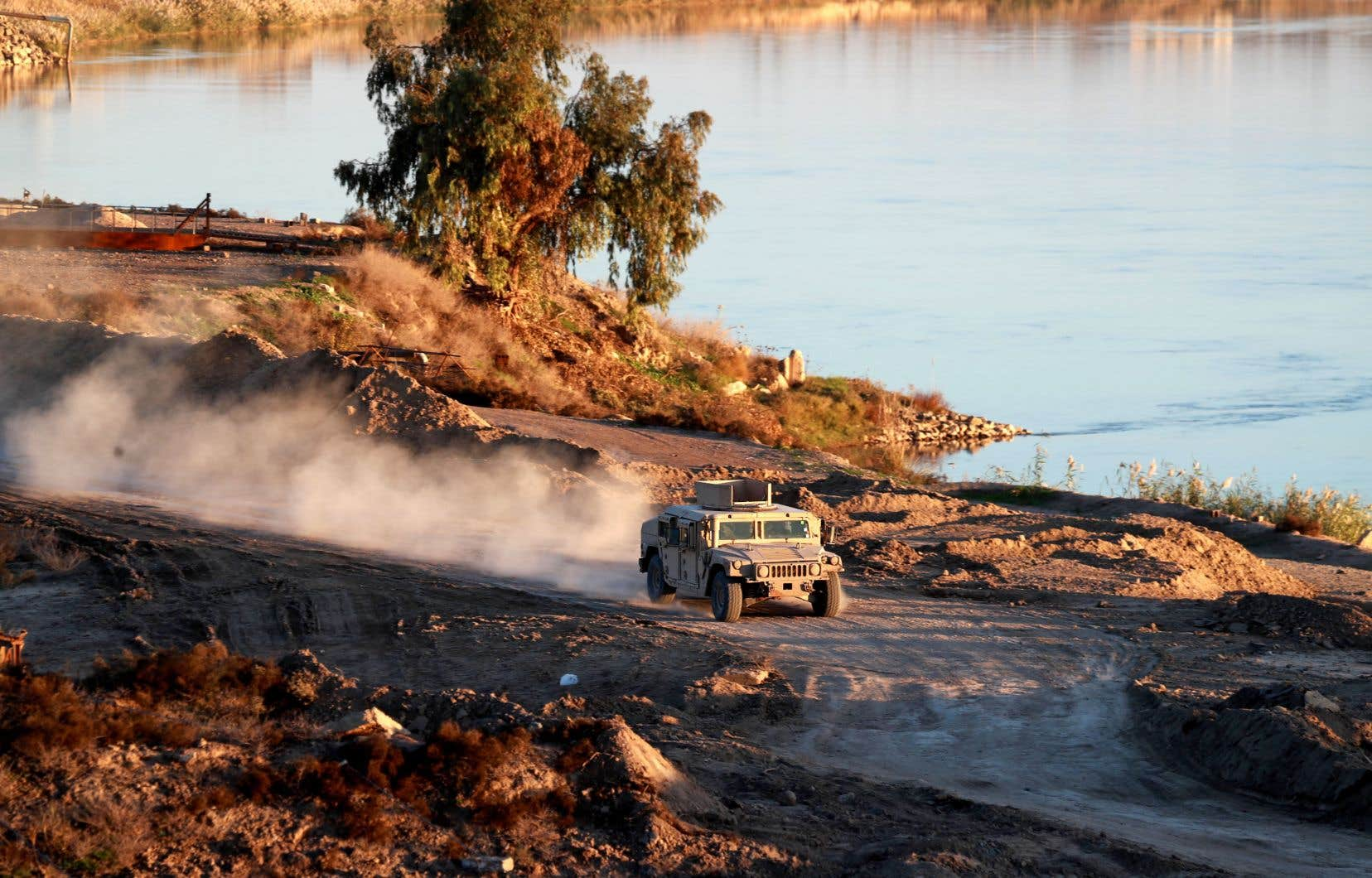 Sur cette photo du 15 décembre, un véhicule de l'armée américaine roule dans l'est de la Syrie. La veille, les Forces démocratiques syriennes, une coalition kurde bénéficiant du soutien de Washington, avait pris le contrôle de Hajin, dernière localité syrienne aux mains du groupe EI.