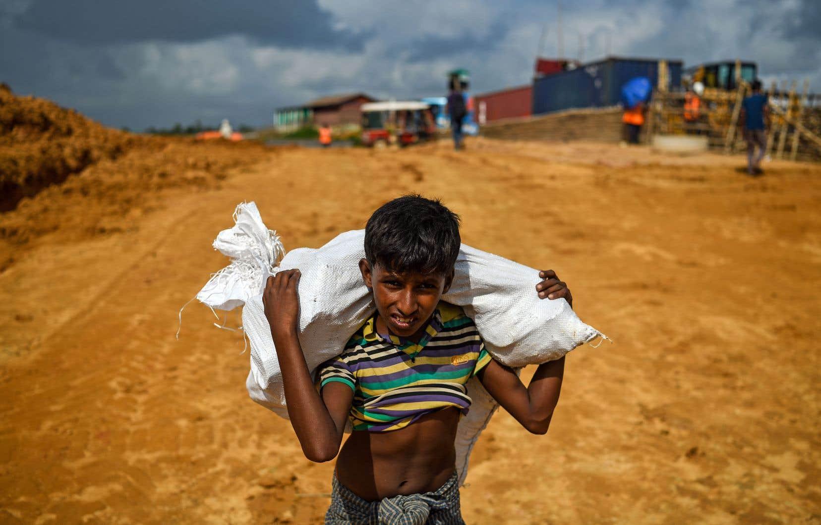 Un jeune garçon rohingya transportant un lourd sac de plastique le long d'une route de terre du camp pour réfugiés Kutupalong, situé dans la ville d'Ukhia au Bangladesh, en août dernier