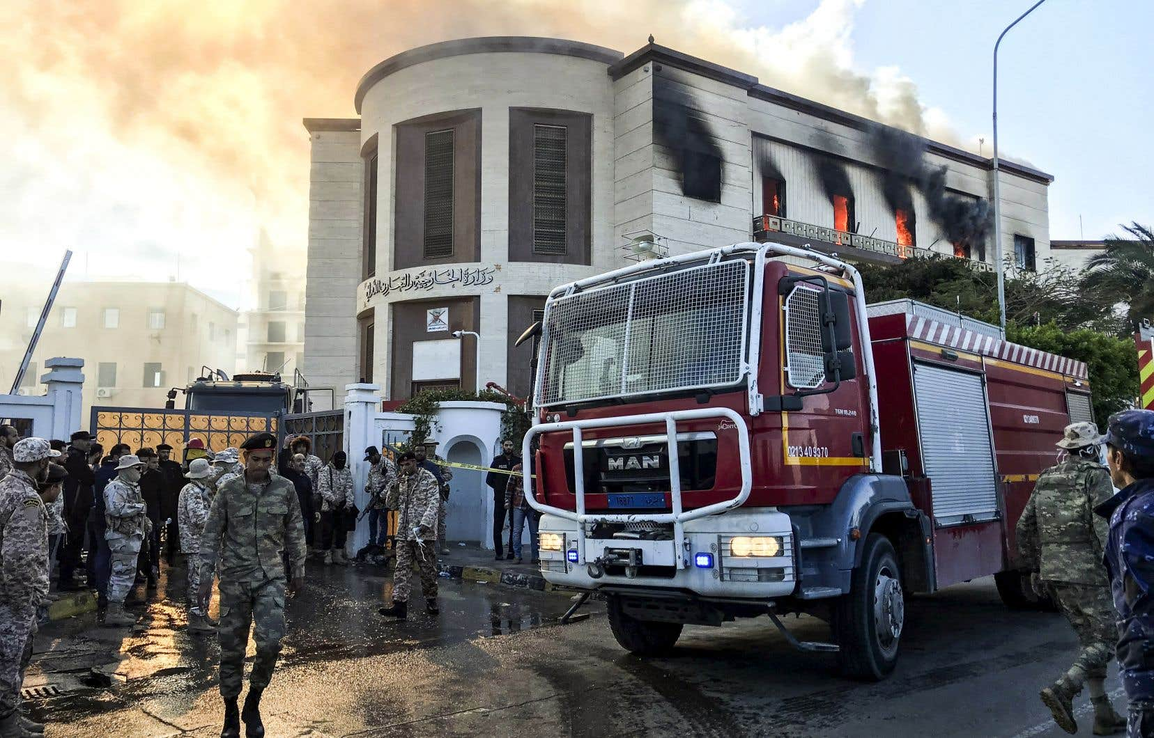 Des pompiers et des soldats sont sur les lieux de l'attaque contre le ministère des Affaires étrangères à Tripoli, mardi.