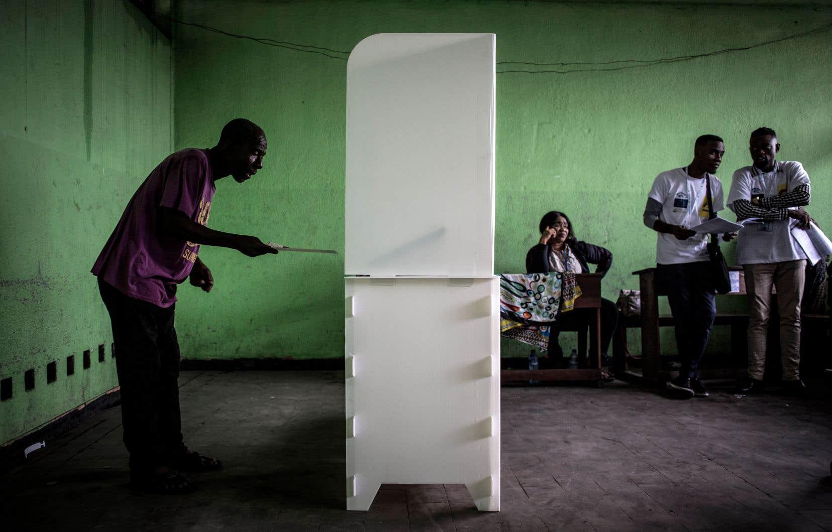 Un Congolais en train d'exercer son droit de vote dans un bureau électoral de la capitale de la RDC, Kinshasa, à l'occasion de la tenue du scrutin présidentiel qui a été reporté à trois reprises depuis deux ans.
