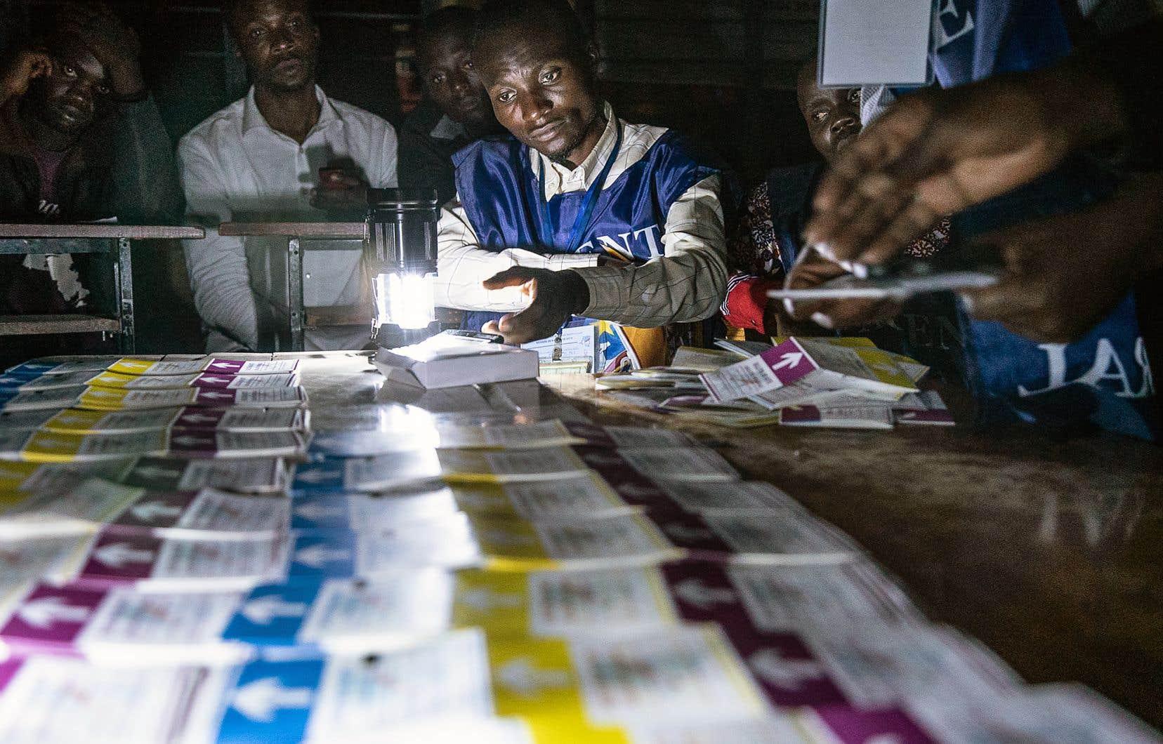 Des agents de la Commission électorale nationale indépendante comptaient des votes, dimanche.