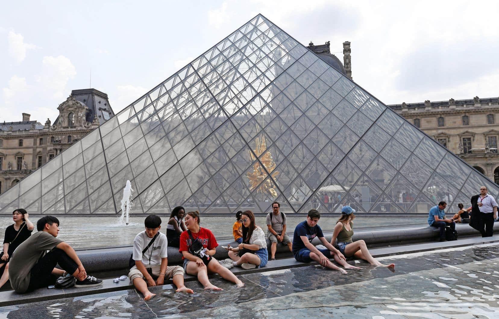 Des visiteurs à la recherche d'un peu de fraîcheur près de la pyramide du Louvre, à Paris, en juillet dernier