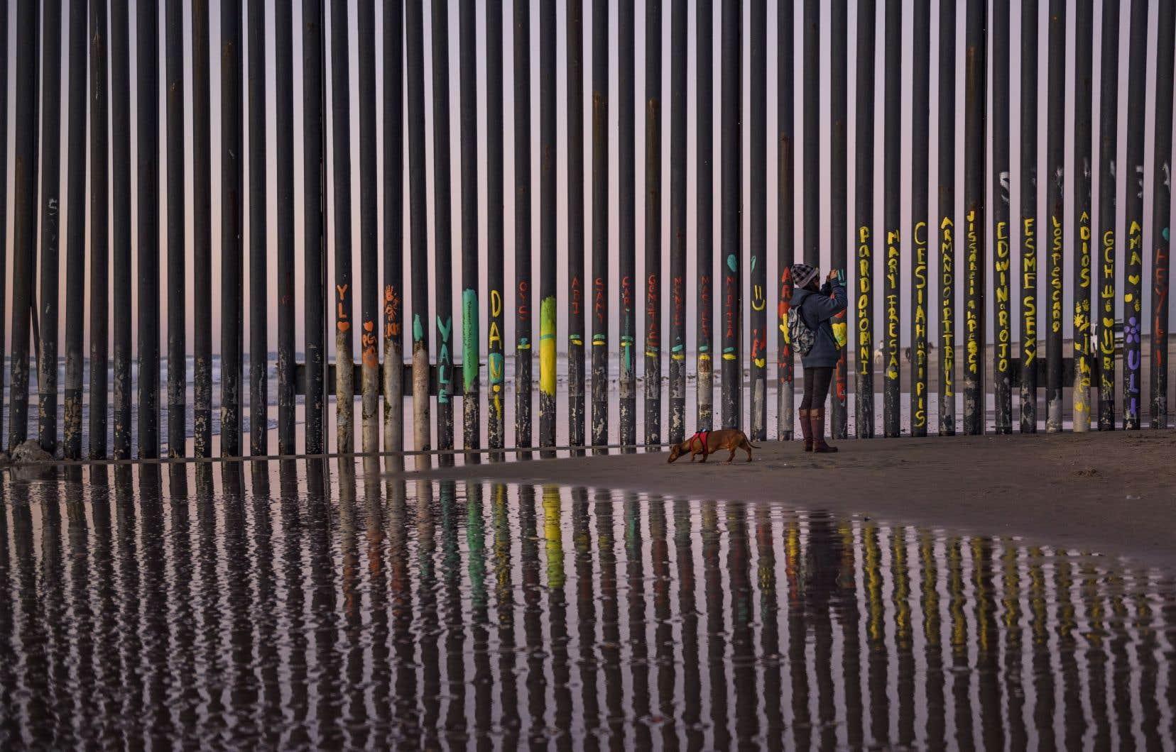 Une femme se promène sur le flanc mexicain de la clôture frontalière qui sépare San Diego, aux États-Unis, et Tijuana, au Mexique.