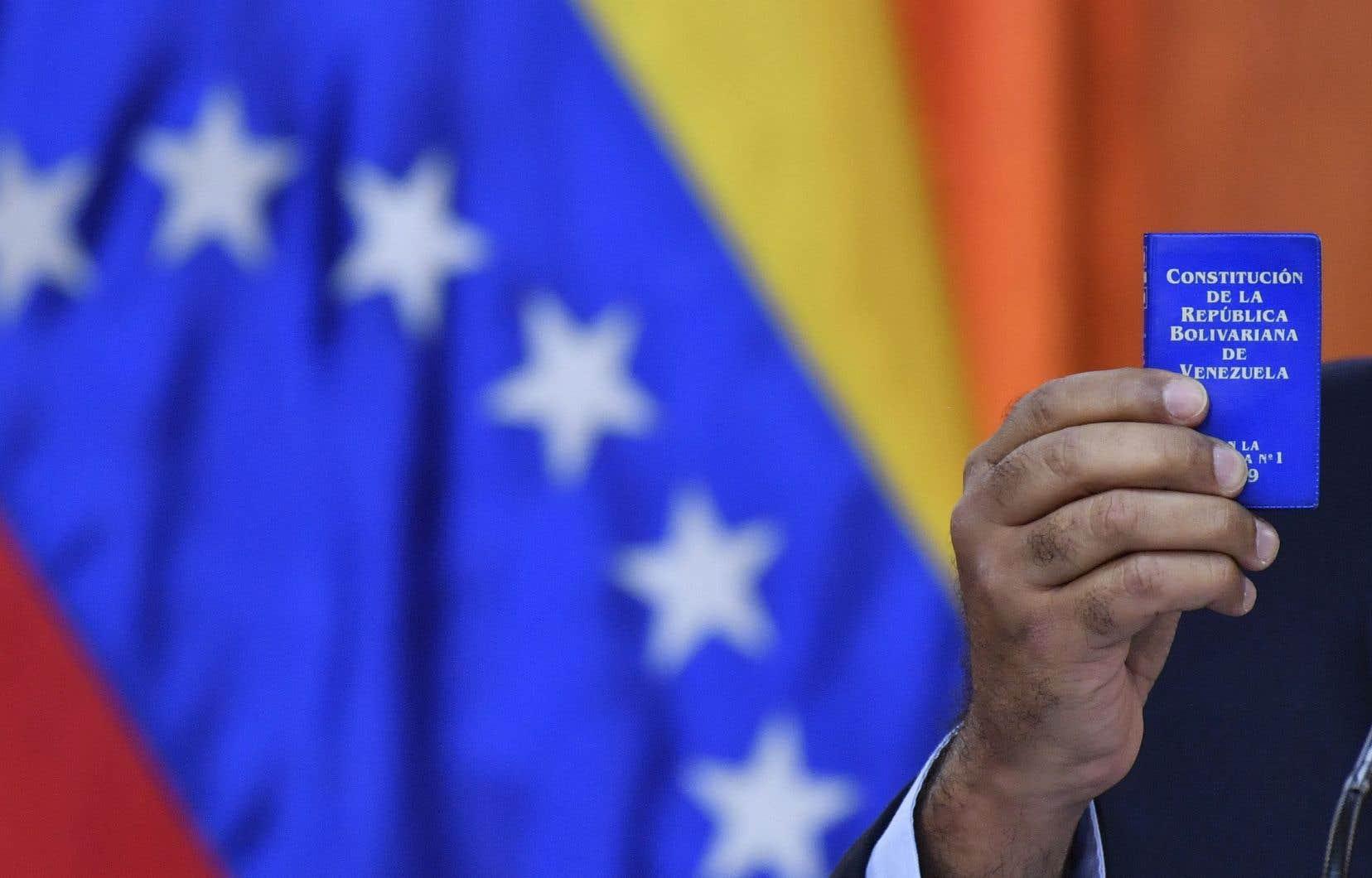 Le président vénézuélien, Nicolas Maduro, brandit la constitution du pays lors d'une conférence de presse à Caracas, le 25 janvier 2019.