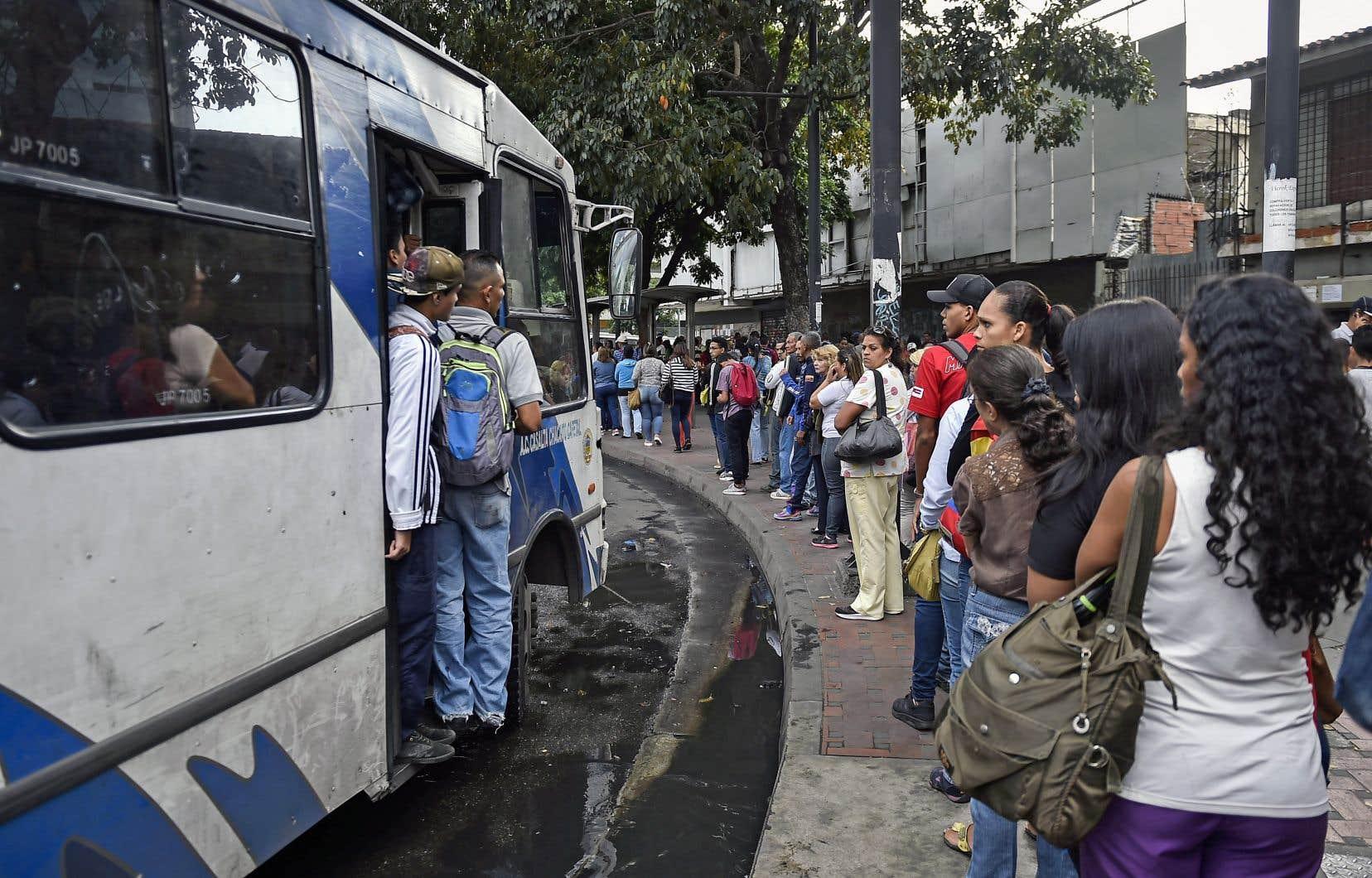 Des Vénézuéliens font la queue en attendant l'autobus, mardi. Les États-Unis ont décidé, lundi, d'imposer des sanctions à la compagnie pétrolière nationale PDVSA, dont ils ont gelé les avoirs à l'étranger, entre autres.