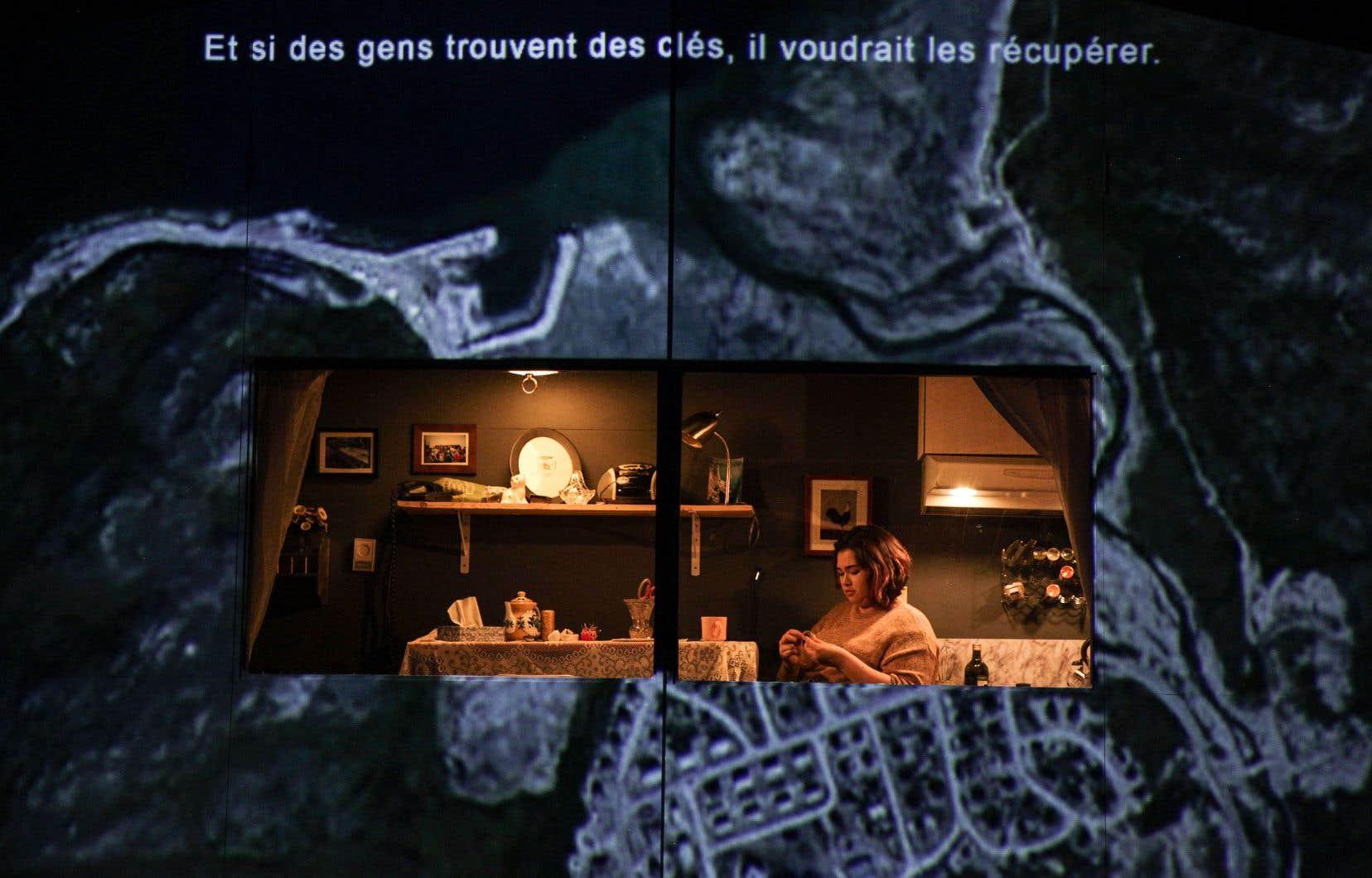 Sur scène, à l'intérieur et autour d'une maison sur laquelle sont projetées des images de paysages nordiques, Hannah Tooktoo interagit sobrement avec le documentaire audio.