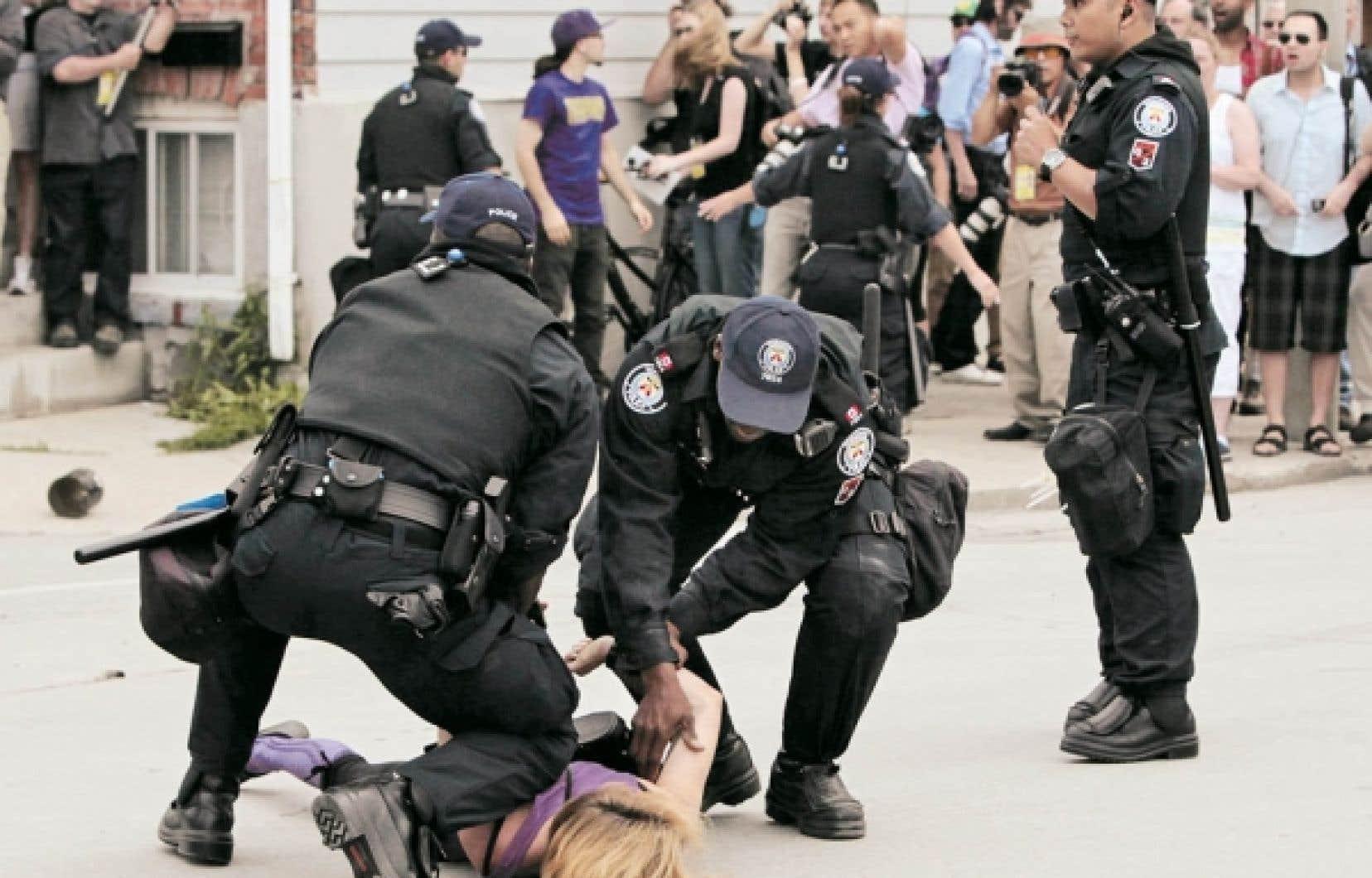 Arrestation d'une jeune femme au cours d'une manifestation au centre-ville de Toronto, dimanche.<br />