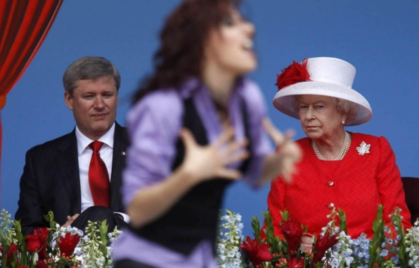 Le premier ministre, Stephen Harper, et la reine Elizabeth II observent une des invités au grand spectacle de la Fête du Canada.<br />