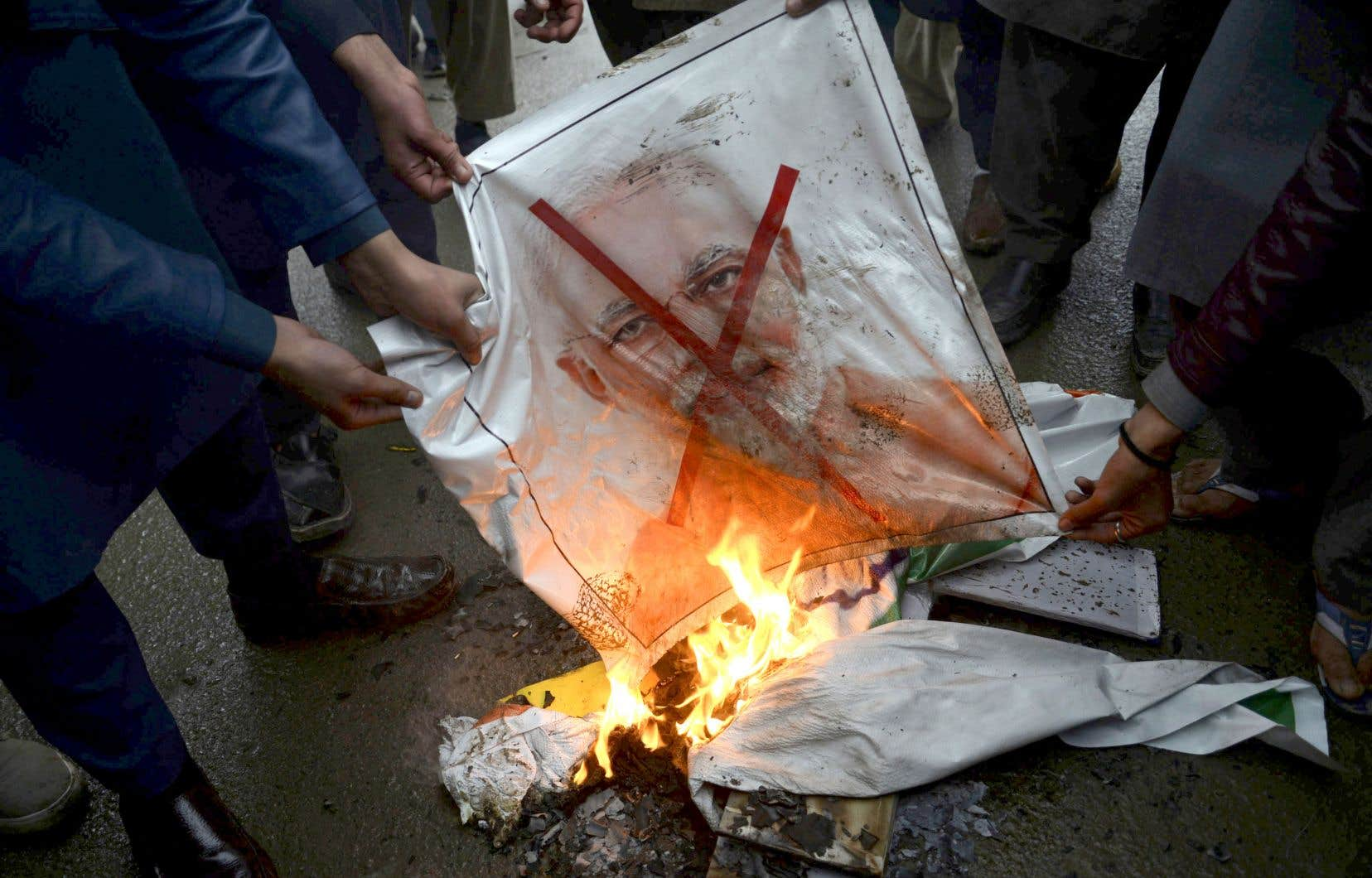 Des manifestants pakistanais brûlent une pancarte à l'effigie du premier ministre indien, Narendra Modi, mardi à Peshawar.