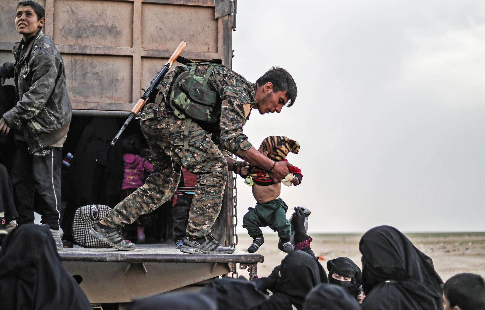 Un combattant des Forces démocratiques syriennes évacuait le 26février des civils de Baghouz, une ville syrienne où le groupe EI tentait toujours dimanche de repousser les offensives des forces arabo-kurdes soutenues par les États-Unis.