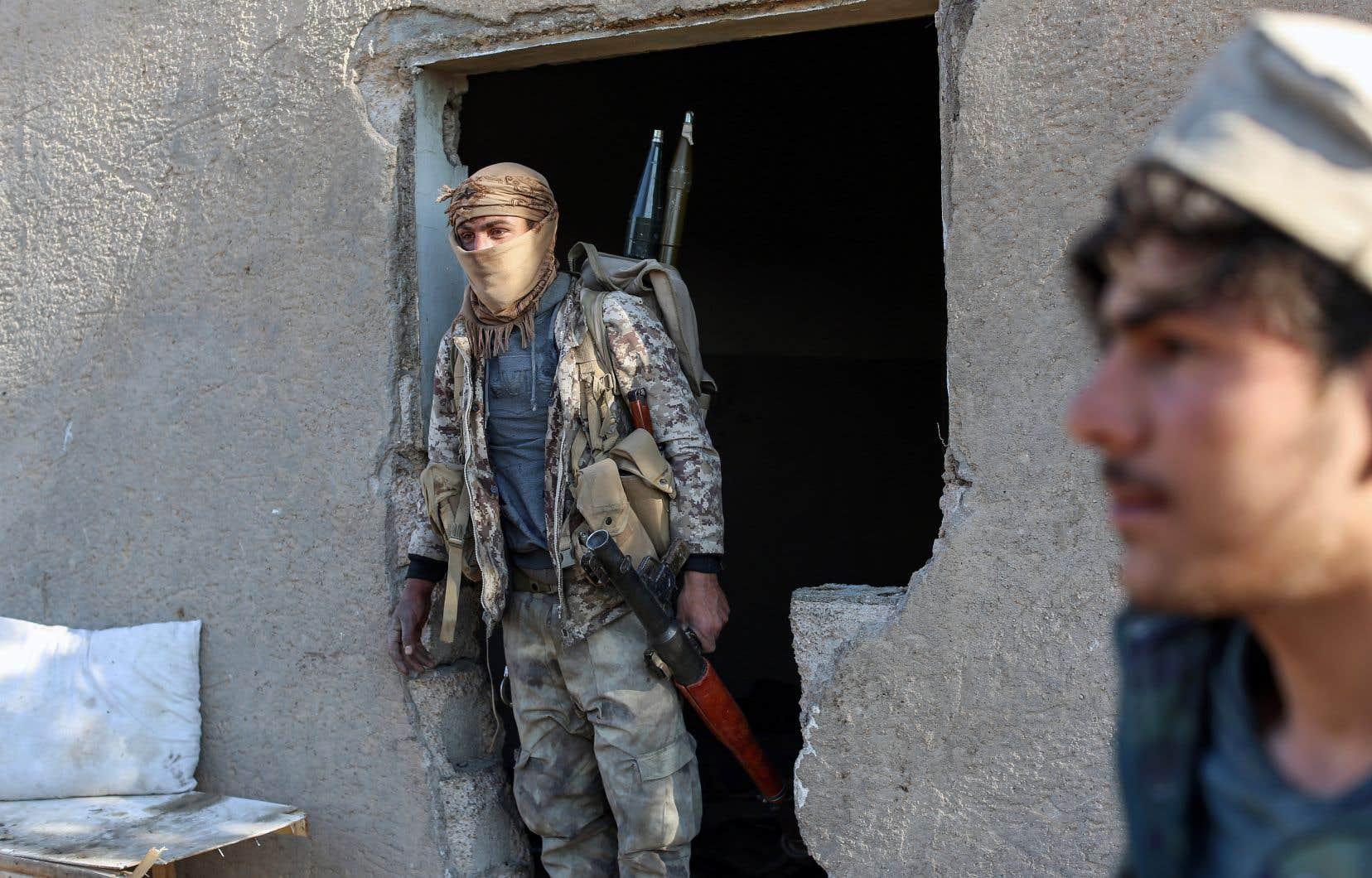 Des combattants des Forces démocratiques syriennes dans un campement de fortune du groupe EI, à Baghouz, samedi