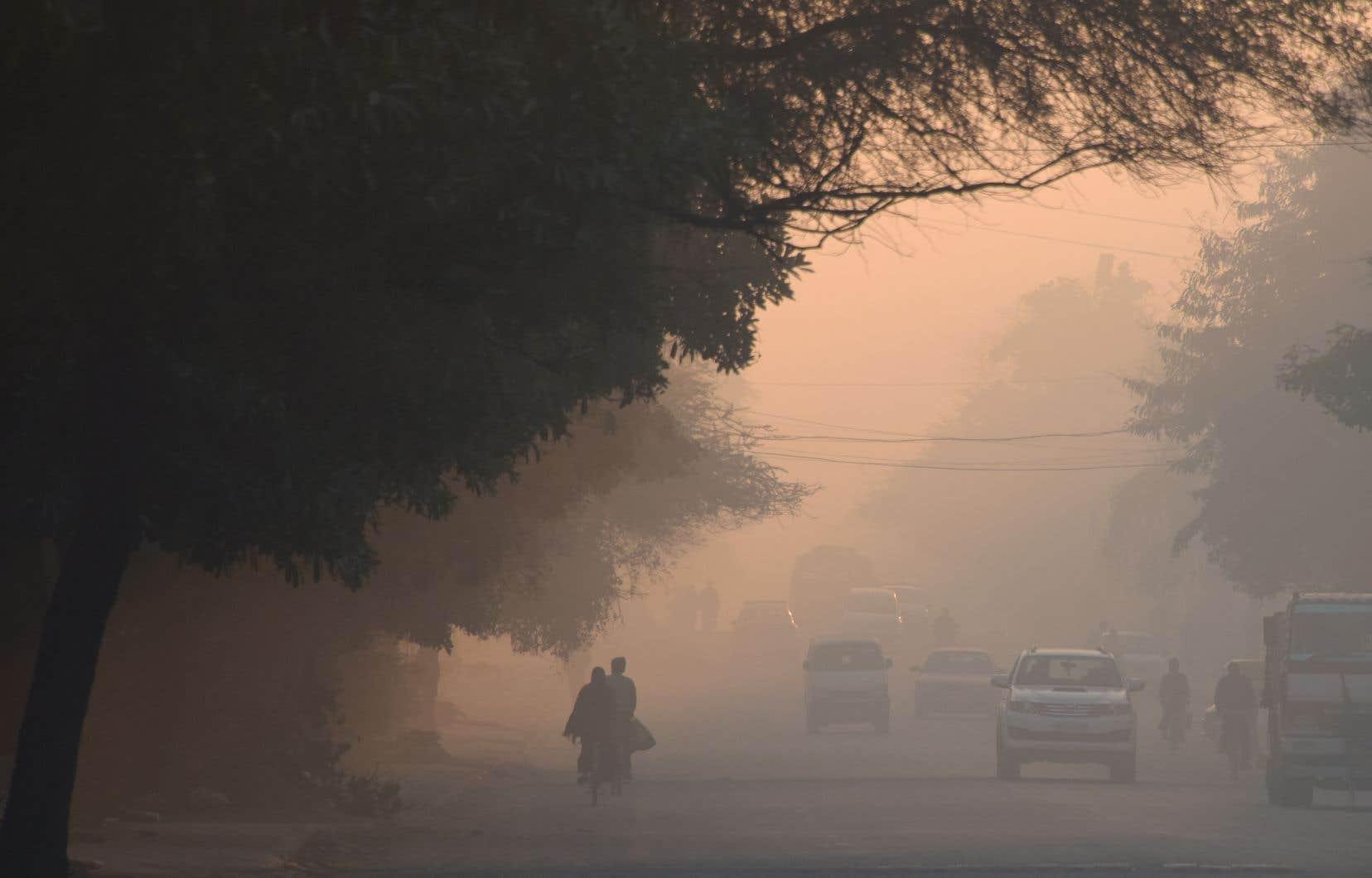 Des Indiens marchent dans un épais smog à Gurgaon le 7 mars 2019, un jour après avoir été placé en tête d'un rapport sur les villes les plus polluées au monde pour 2018.