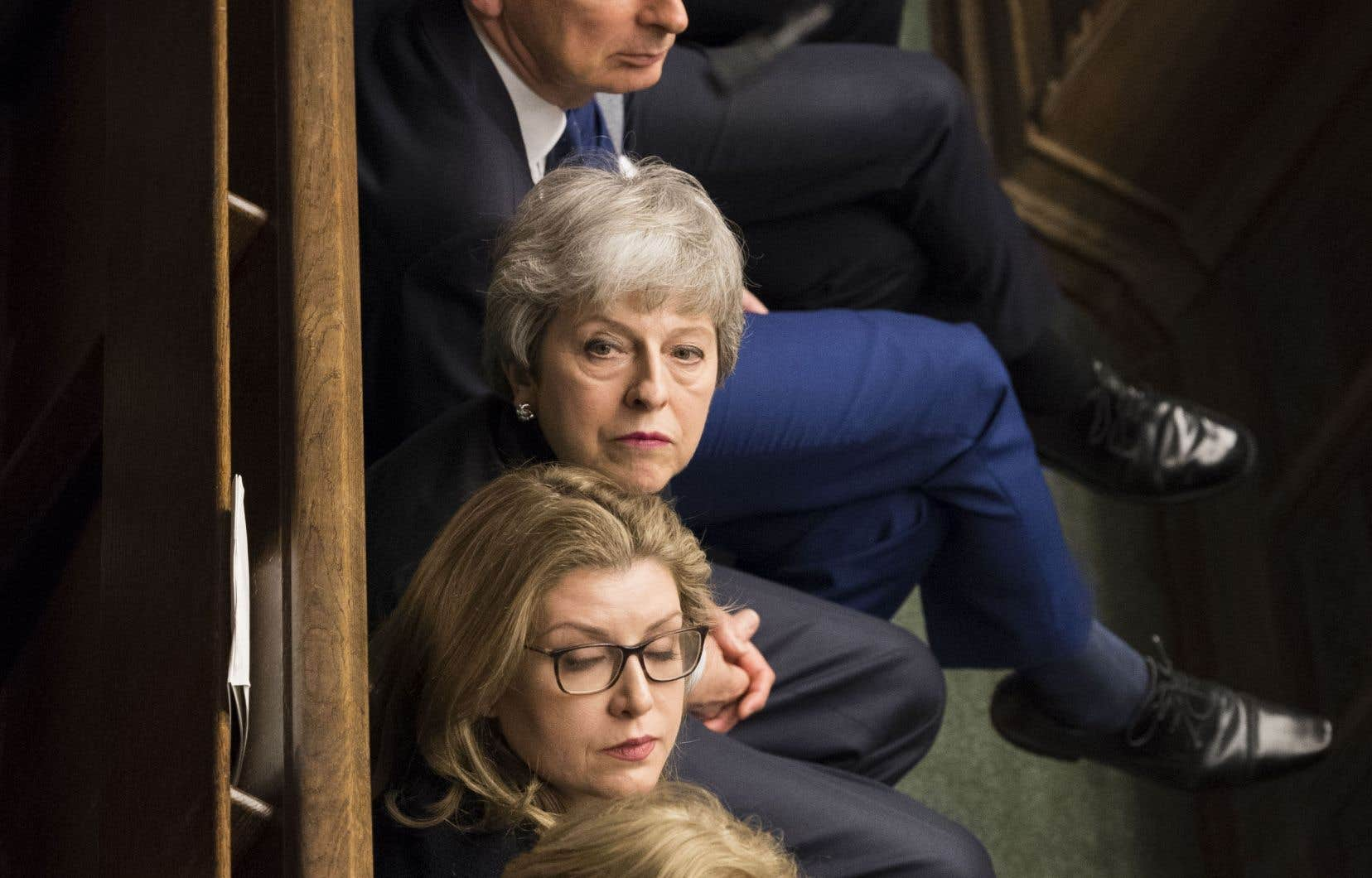 Theresa May tend l'oreille lors de la période de questions au parlement britannique, mercredi.