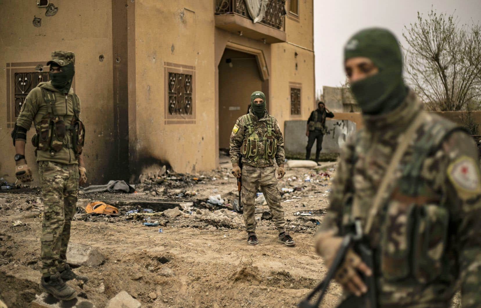 Des combattants des Forces démocratiques syriennes arpentaitent dimanche le village de Baghouz, en Syrie, au lendemain de la victoire contre le groupe armé État islamique.