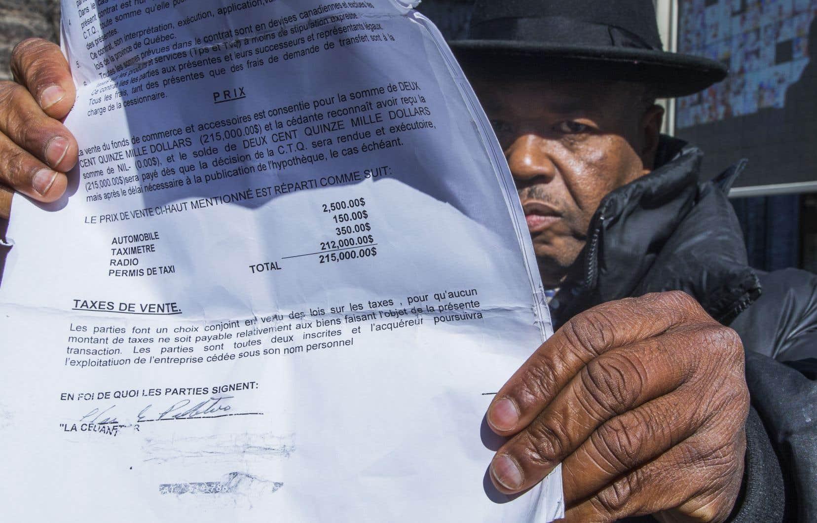 Les chauffeurs de taxi ne cessent de répéter que les 500 millions mis sur la table par le gouvernement ne suffiront pas à éponger leurs pertes. Celui-ci montre le contrat d'achat de son permis, pour lequel il a investi 215 000$.