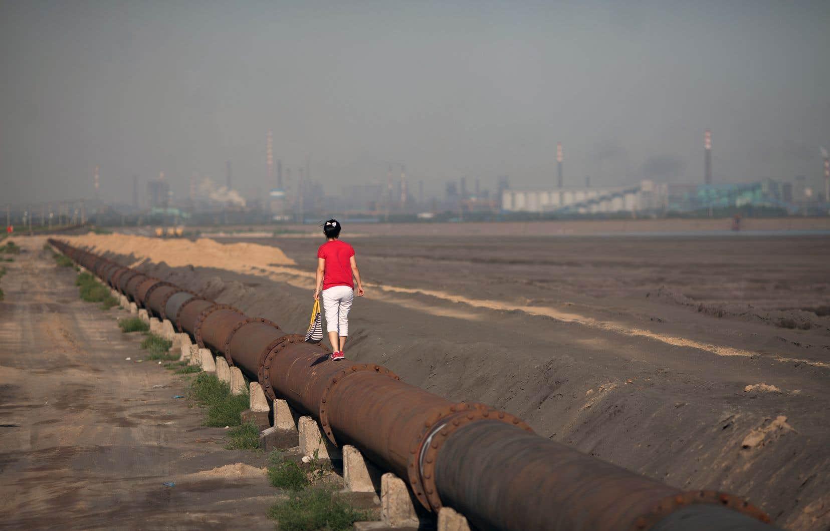 Une femme se tient debout sur un pipeline tout près d'un «lac toxique» entouré de raffineries de terres rares près de la ville de Baotou, en Mongolie intérieure.