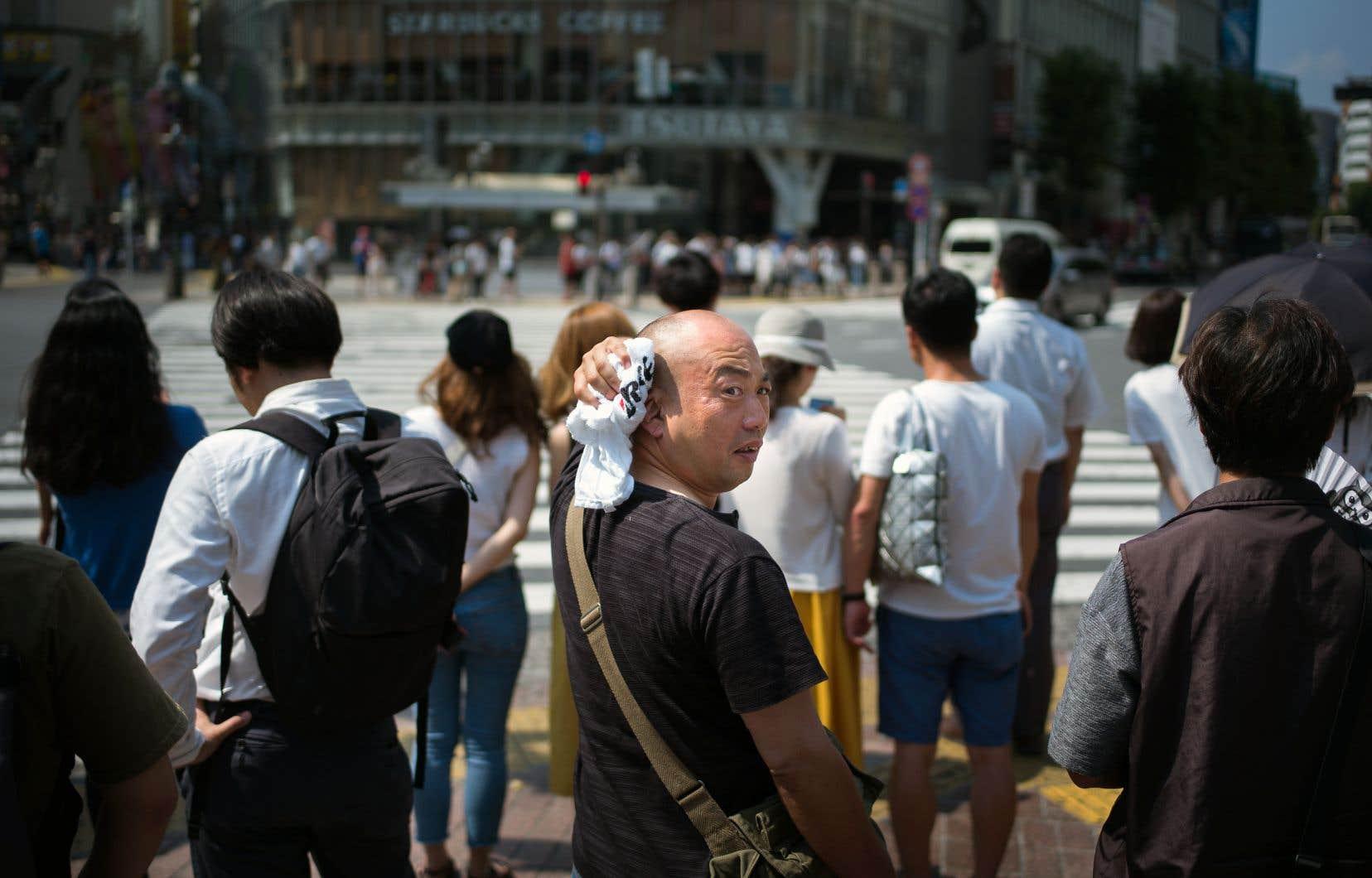 Un homme s'épongeant le cou à une intersection de Tokyo, le 24juillet dernier, alors que le Japon traversait une vague de chaleur qui a fait plus d'une soixantaine de morts.