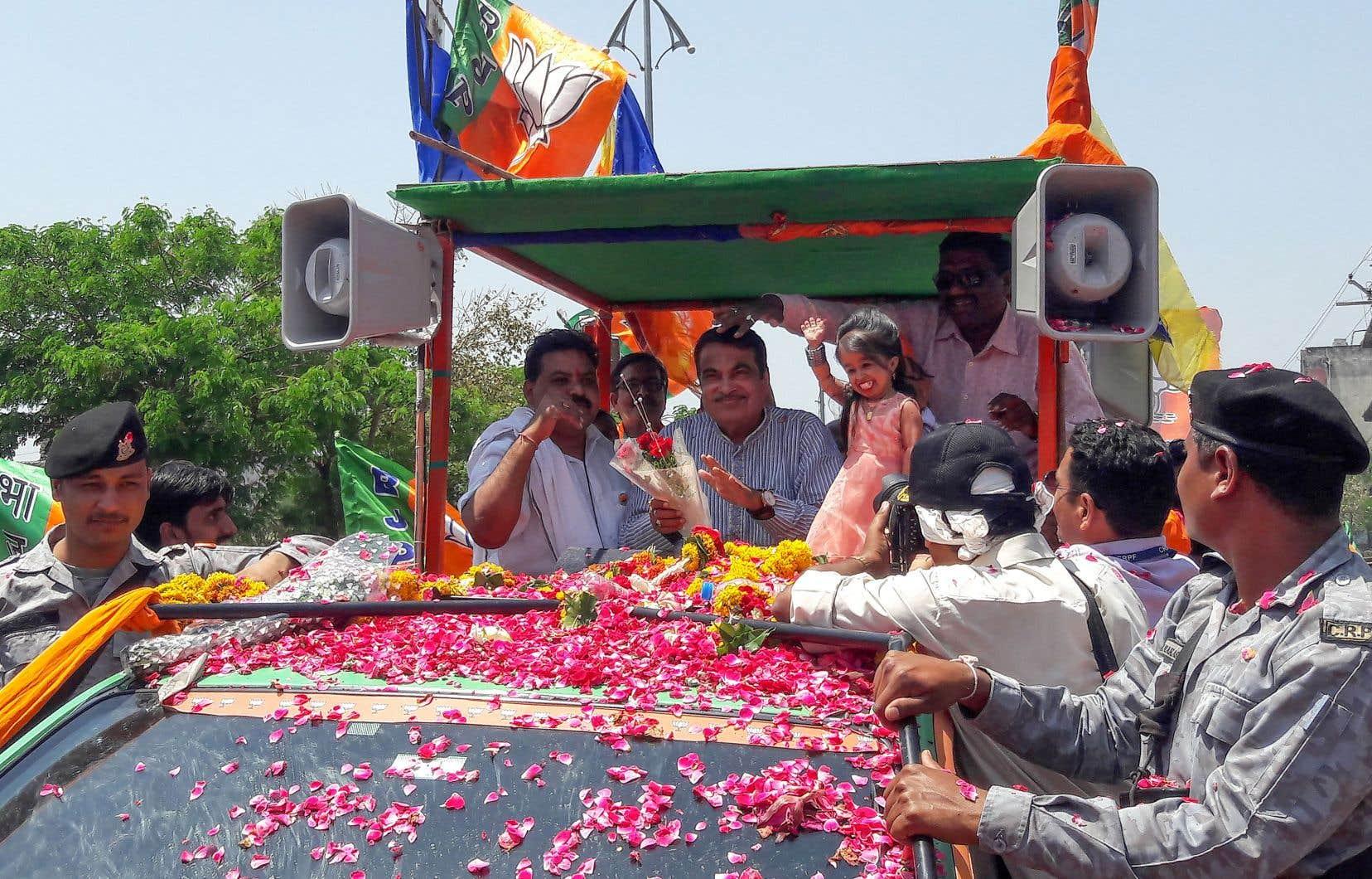 Le candidat local du parti BJP à Nagpur, Nitin Gadkari, accompagné de Jyoti Amge, considérée comme la plus petite femme au monde, est salué par ses partisans à l'occasion d'un défilé politique.