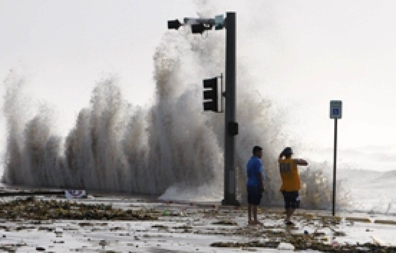 Des citoyens de Galveston, au Texas, observant l'océan en fureur, hier après-midi.