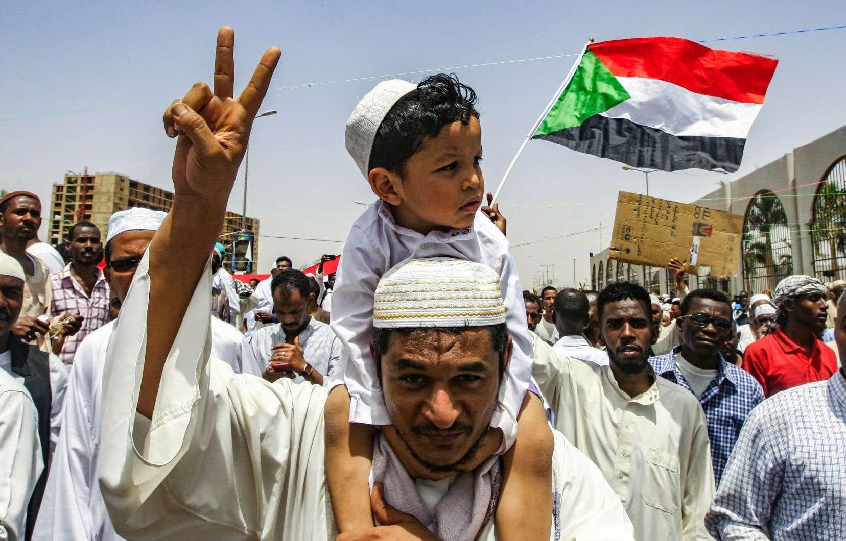 Un manifestant lance le geste de victoire alors qu'il marchait avec d'autres au cours d'un rassemblement devant le siège de l'armée à Khartoum, la capitale soudanaise, le 12 avril 2019.