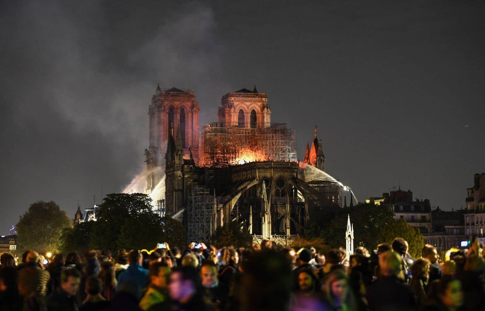 La foule, massée lundi le long des quais de Seine, assiste, pétrifiée, à la disparition d'une partie de la mythique cathédrale.