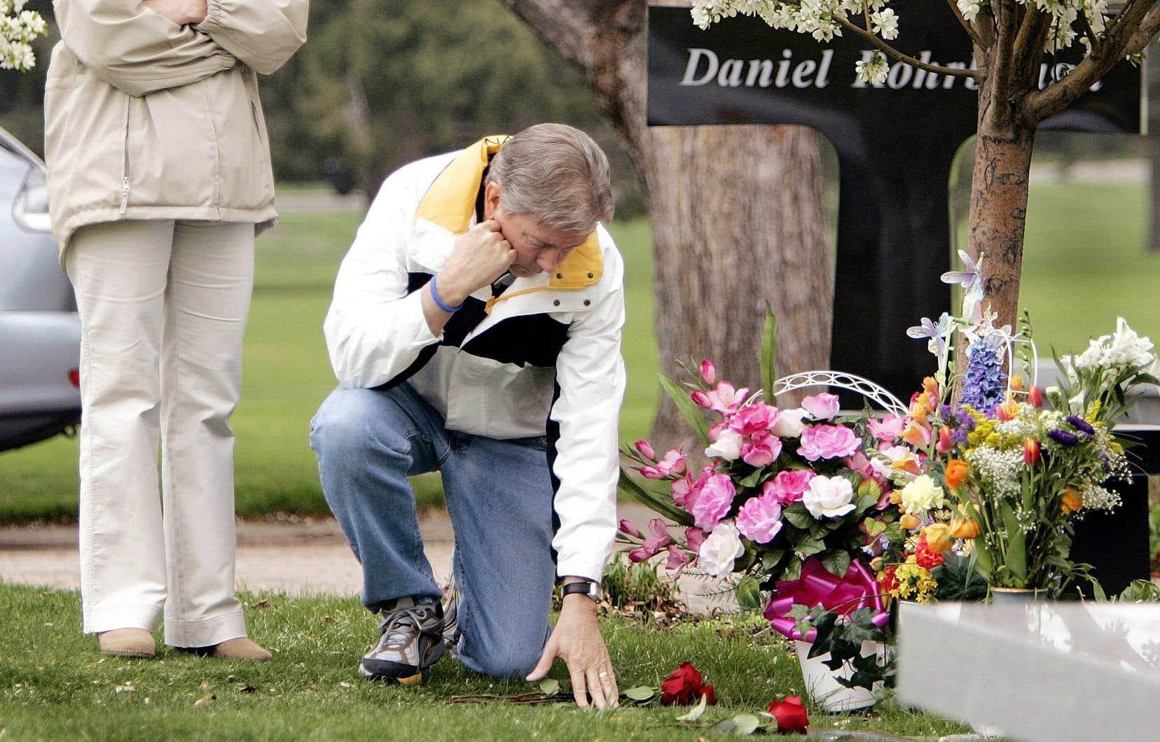 Darrell Scott touchant le sol où sa fille Rachel est enterrée, en avril 2005, six ans après sa mort. La jeune fille est l'une des treize personnes qui sont tombées sous les balles de deux étudiants à l'école secondaire de Columbine, au Colorado, en 1999.