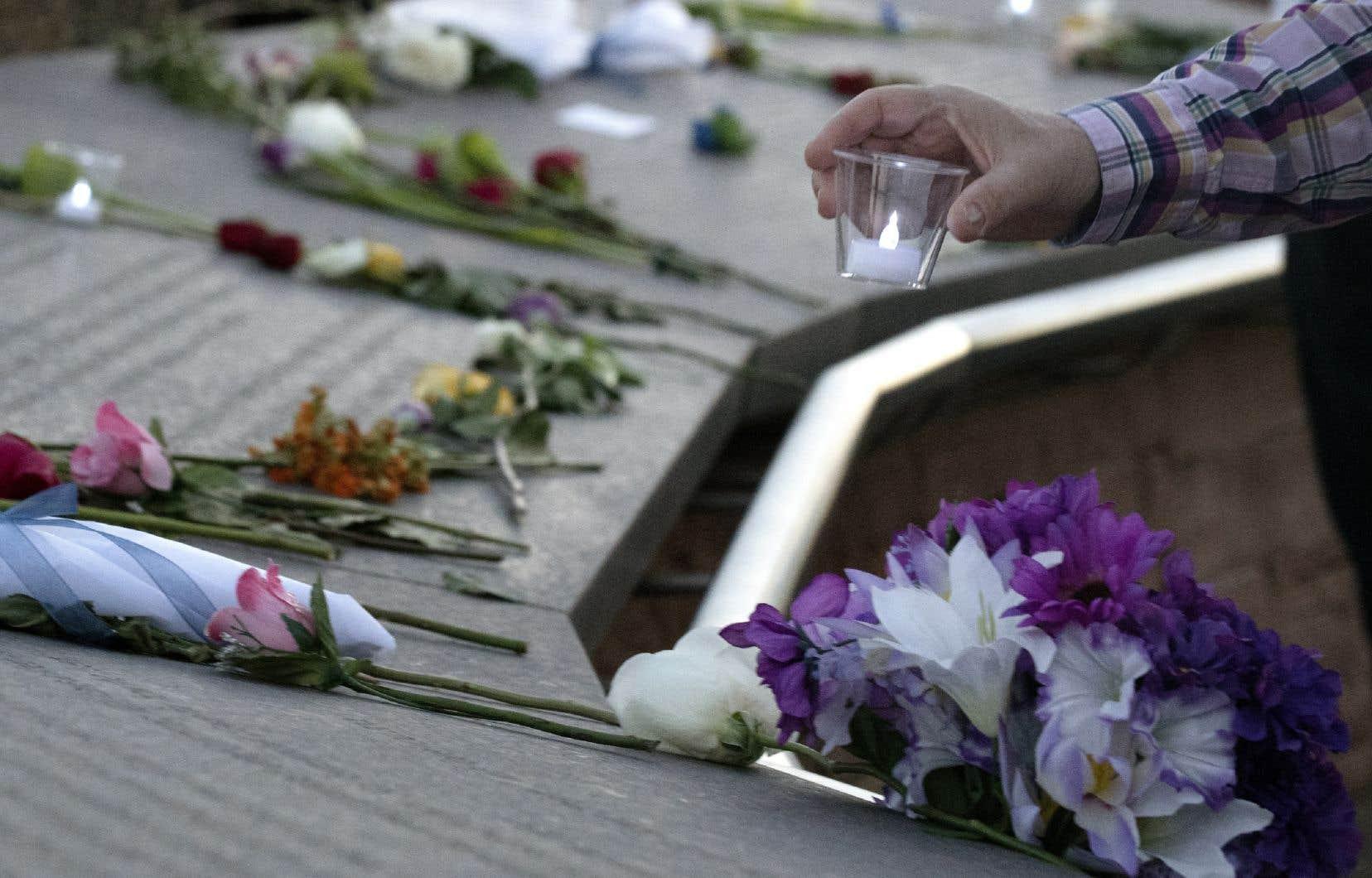 Un visiteur place une bougie parmi des fleurs sur le monument commémoratif Columbine au Clement Park de Littleton, dans le Colorado, à l'occasion du 20e anniversaire de la tuerie de l'école Columbine.