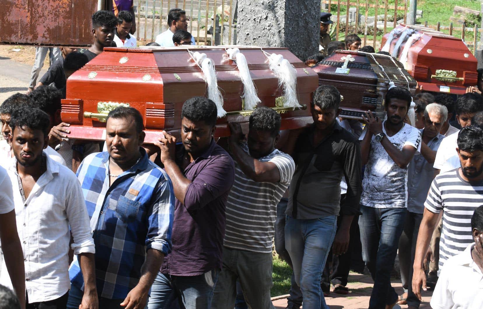 Des proches des victimes des attentats portent des cercueils lors d'un enterrement dans un cimetière à Colombo le 23 avril 2019.