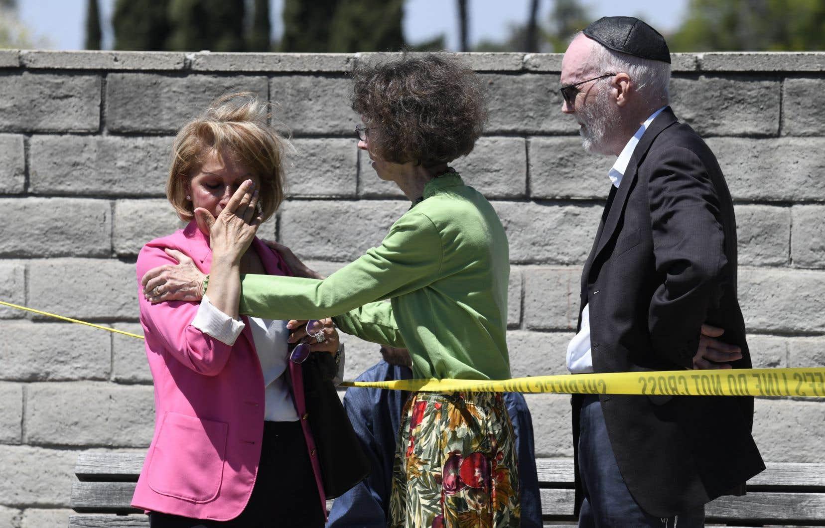 Des membres de la congrégation se consolent devant la synagogue Chabad of Poway, en Californie.