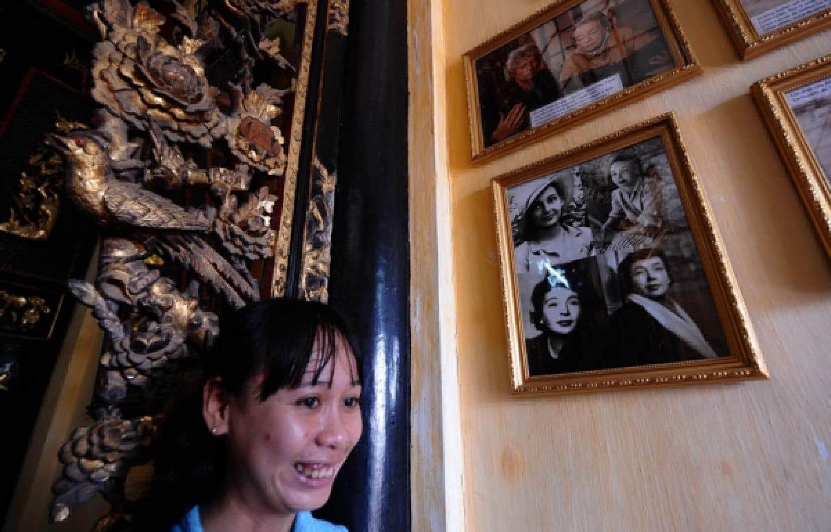 La guide Le Thi Thanh Tuyen pose devant des photographies de Marguerite Duras dispers&eacute;es sur les murs de la maison de l&rsquo;Amant, &agrave; Sadec, maintenant ouverte au public.<br />