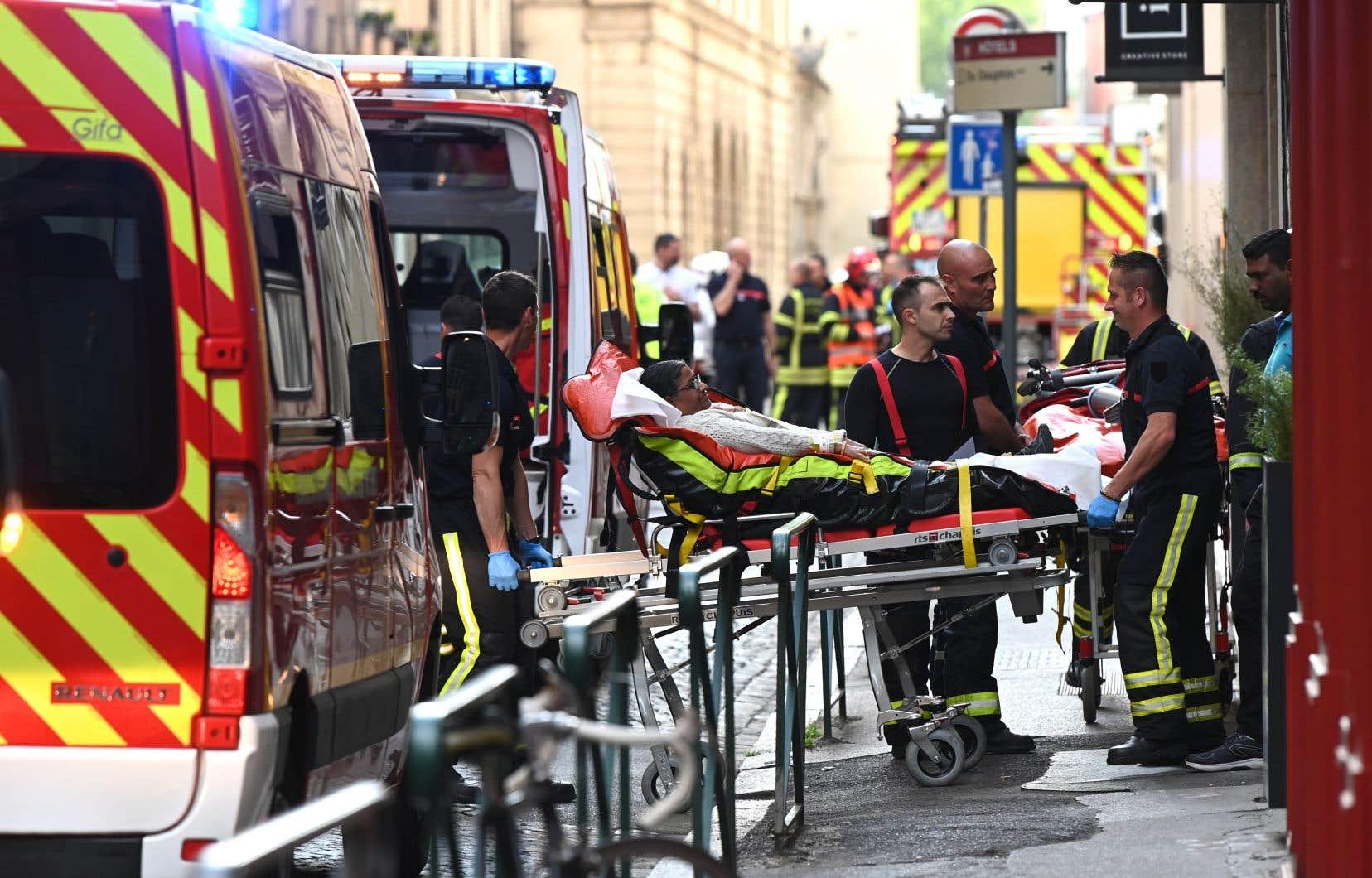 Des secouristes transportent en lieu sûr une des personnes blessées par l'explosion de ce qui semble être un colis piégé dans une rue piétonnière de Lyon.