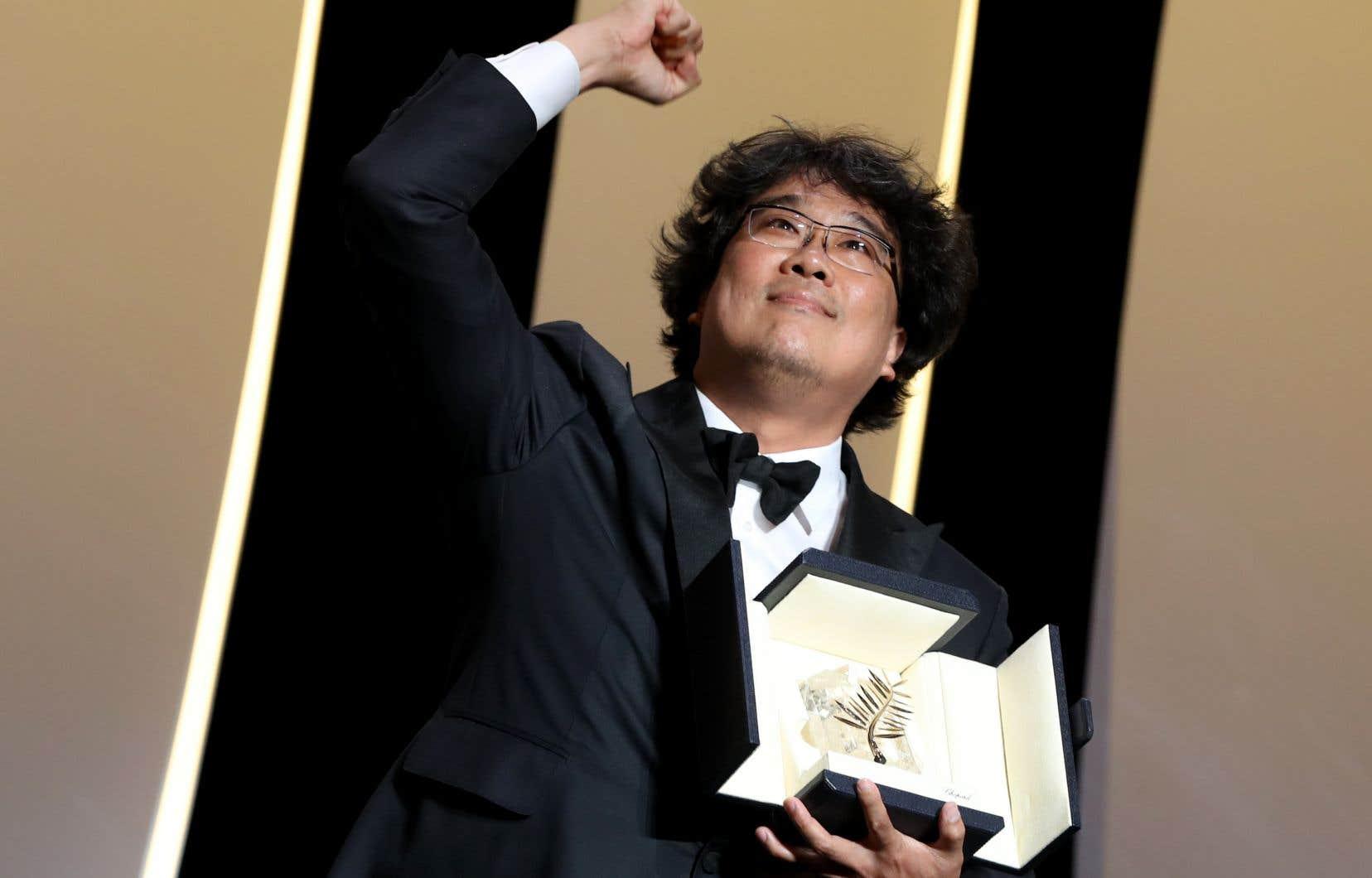 Le réalisateur sud-coréen Bong Joon-Ho pose sur scène avec son trophée après avoir reçu la Palme d'or au Festival de Cannes pour le film «Parasite», le 25 mai 2019.