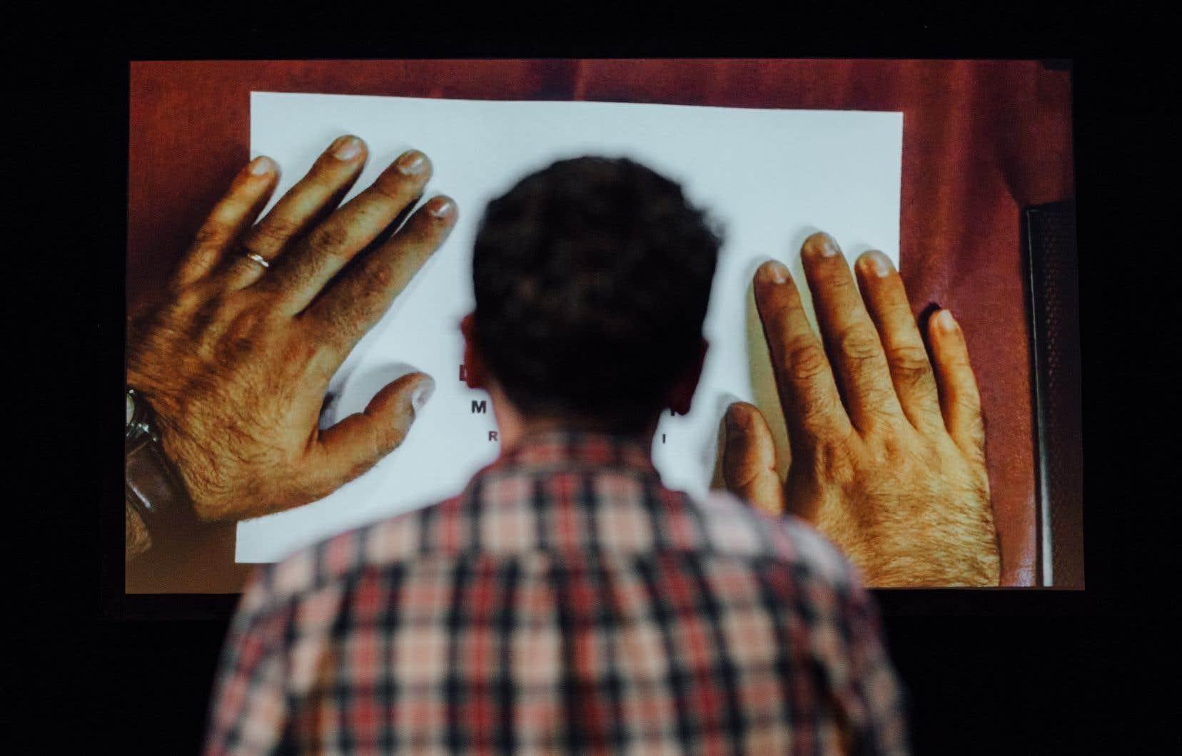 Ses mains projetées sur un écran en fond de scène, Nassim tourne les pages et accompagne la comédienne à qui il demande de raconter son histoire pour lui.