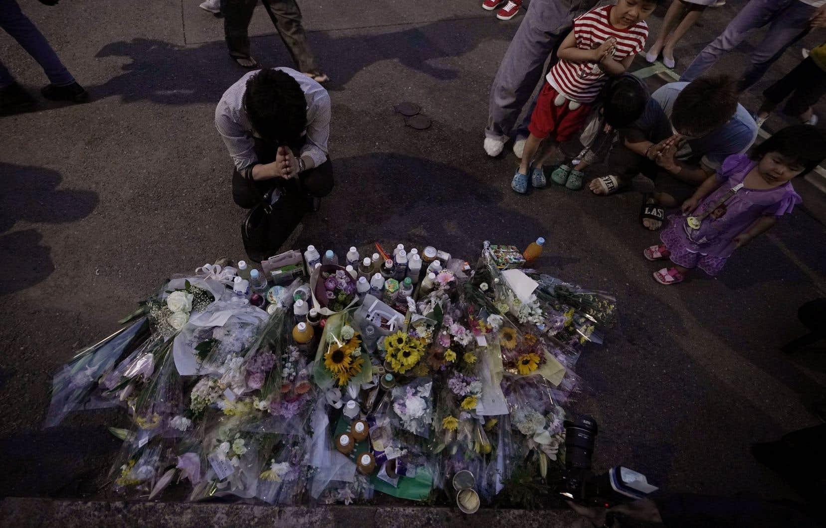 Des gens rendent hommage des victimes de l'attaque au couteau devant un mémorial, mardi le 28 mai 2019 à Kawasaki, près de Tokyo.